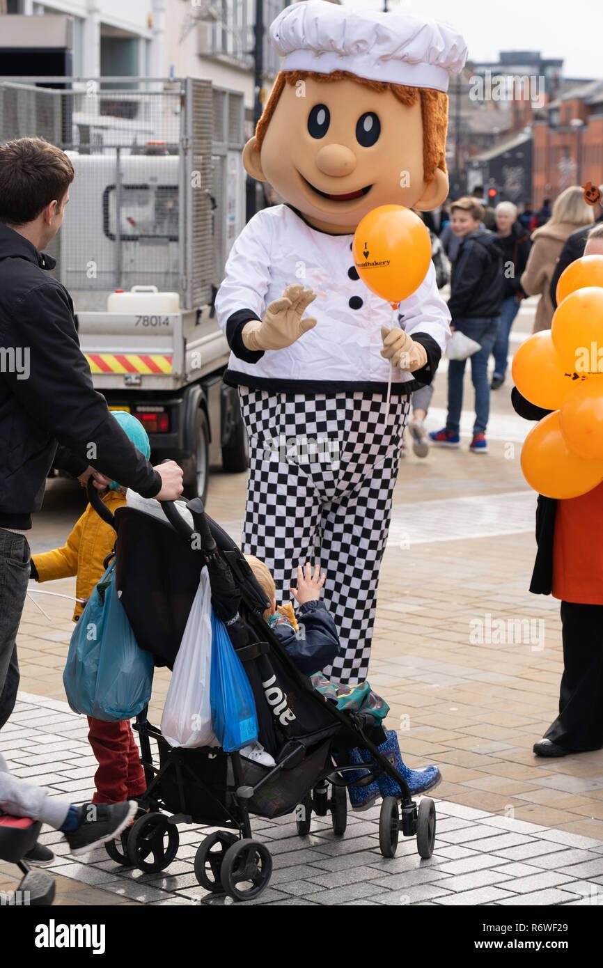 Bakery Mascot handing out orange balloons in Leeds,Briggate,West Yorkshire,England,UK. - Stock Image