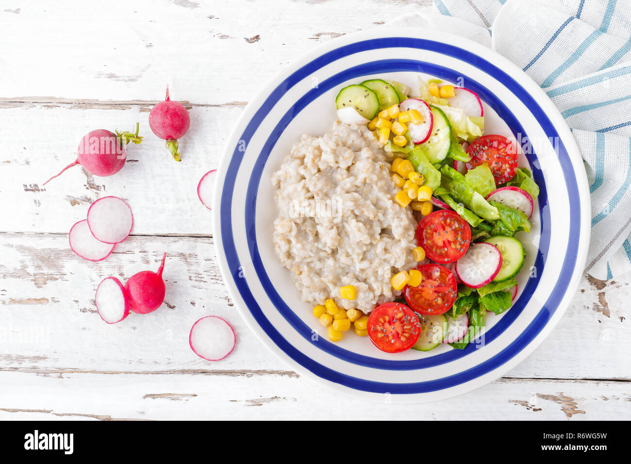 Oatmeal porridge with vegetable salad of fresh tomatoes, corn, cucumber and lettuce. Light, healthy and tasty dietary breakfast. Top view - Stock Image