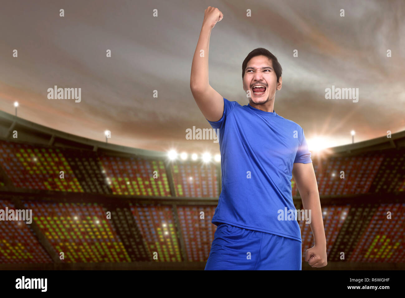 Excited asian footballer with blue jersey celebrating - Stock Image