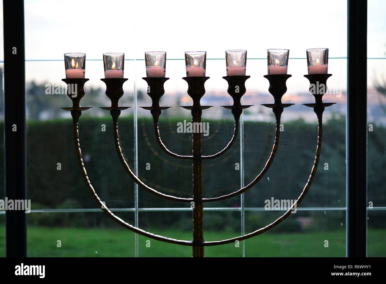 beautiful Menorah jewish 7 armed lampstand standing in window, mount zion in background JERUSALEM ISRAEL - Stock Image