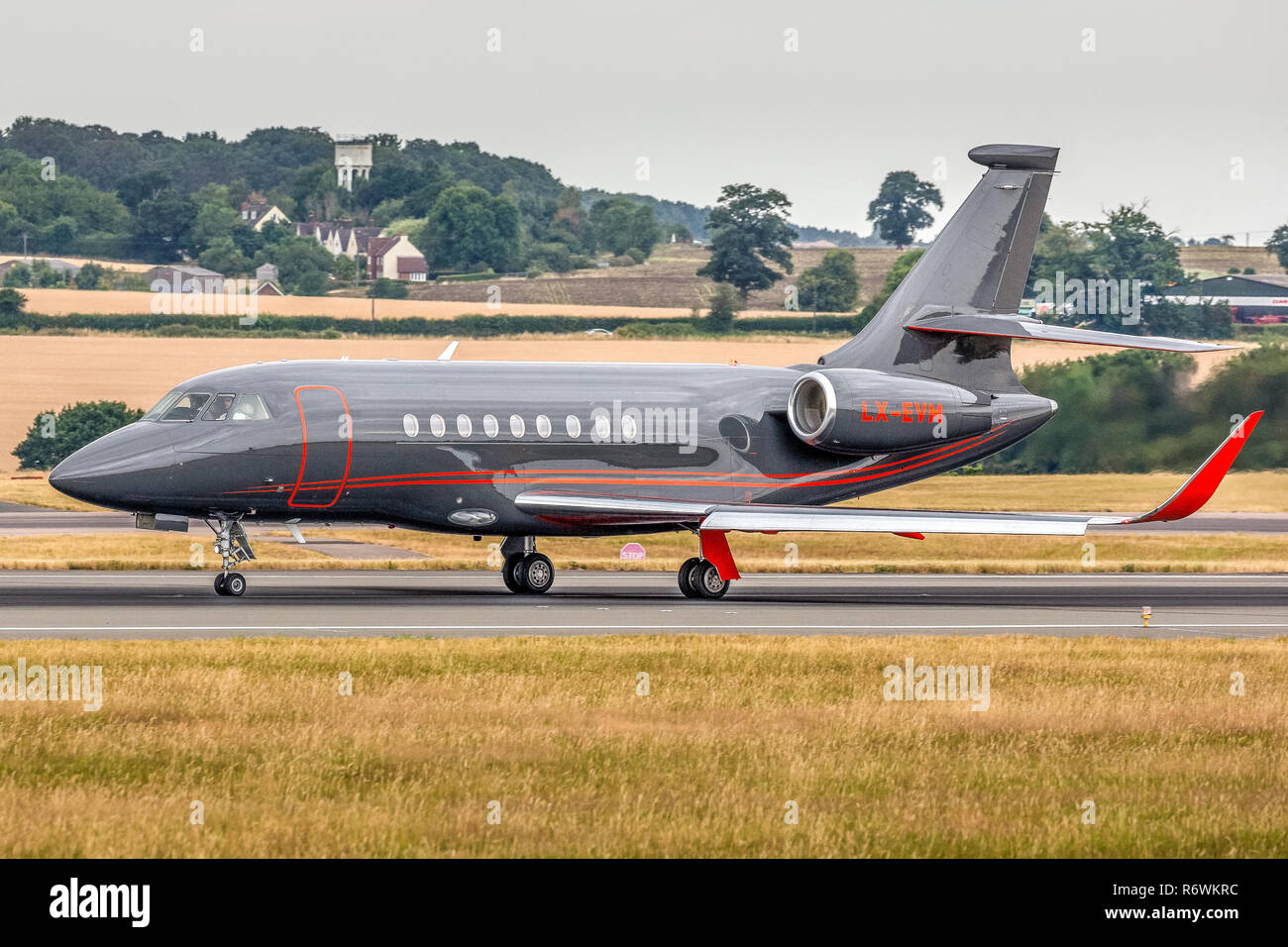 A Dassault Falcon 2000EX Executive Business jet, registered in Luxembourg as LX-EVM, taxying on the runway at London Luton Airport in England. - Stock Image