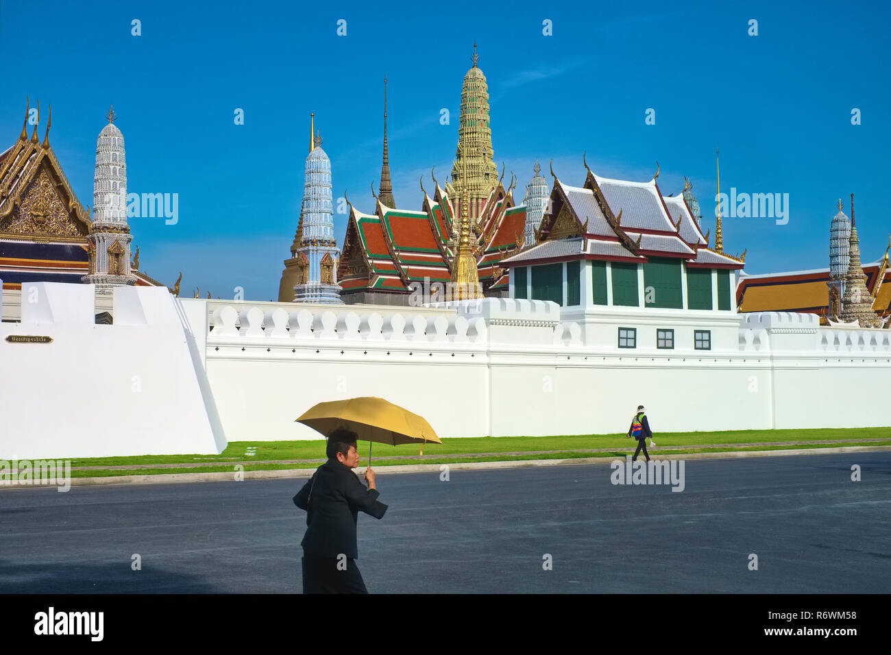 Pedestrians walking past the impressive skyline of Wat Phra Kaew (Gaew) and the Grand Palace in Bangkok, Thailand, the country's most revered temple - Stock Image
