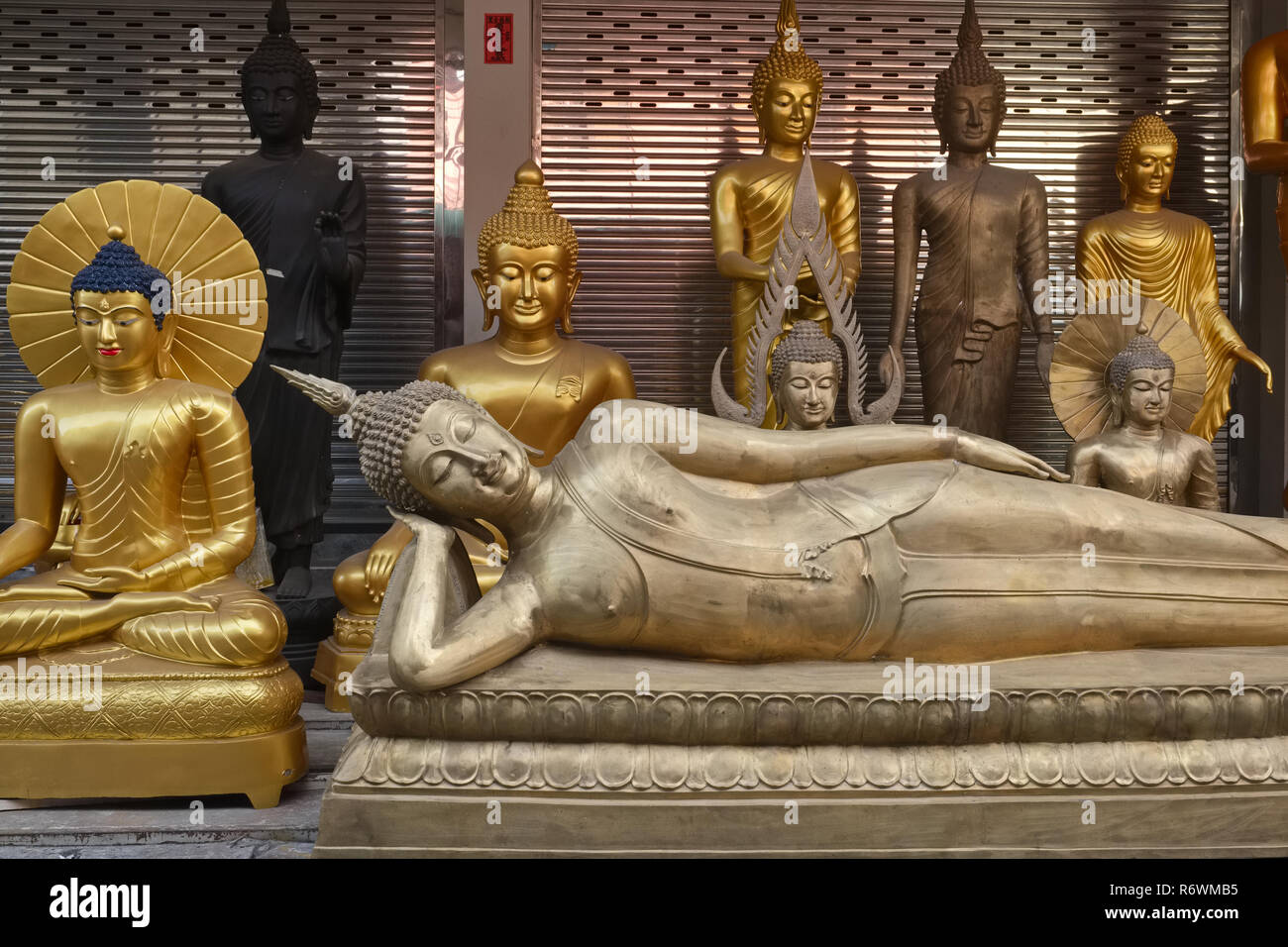 A Reclining Buddha and other Buddha statues outside a factory outlet for religious artifacts in Bamrung Muang Road, Bangkok, Thailand - Stock Image