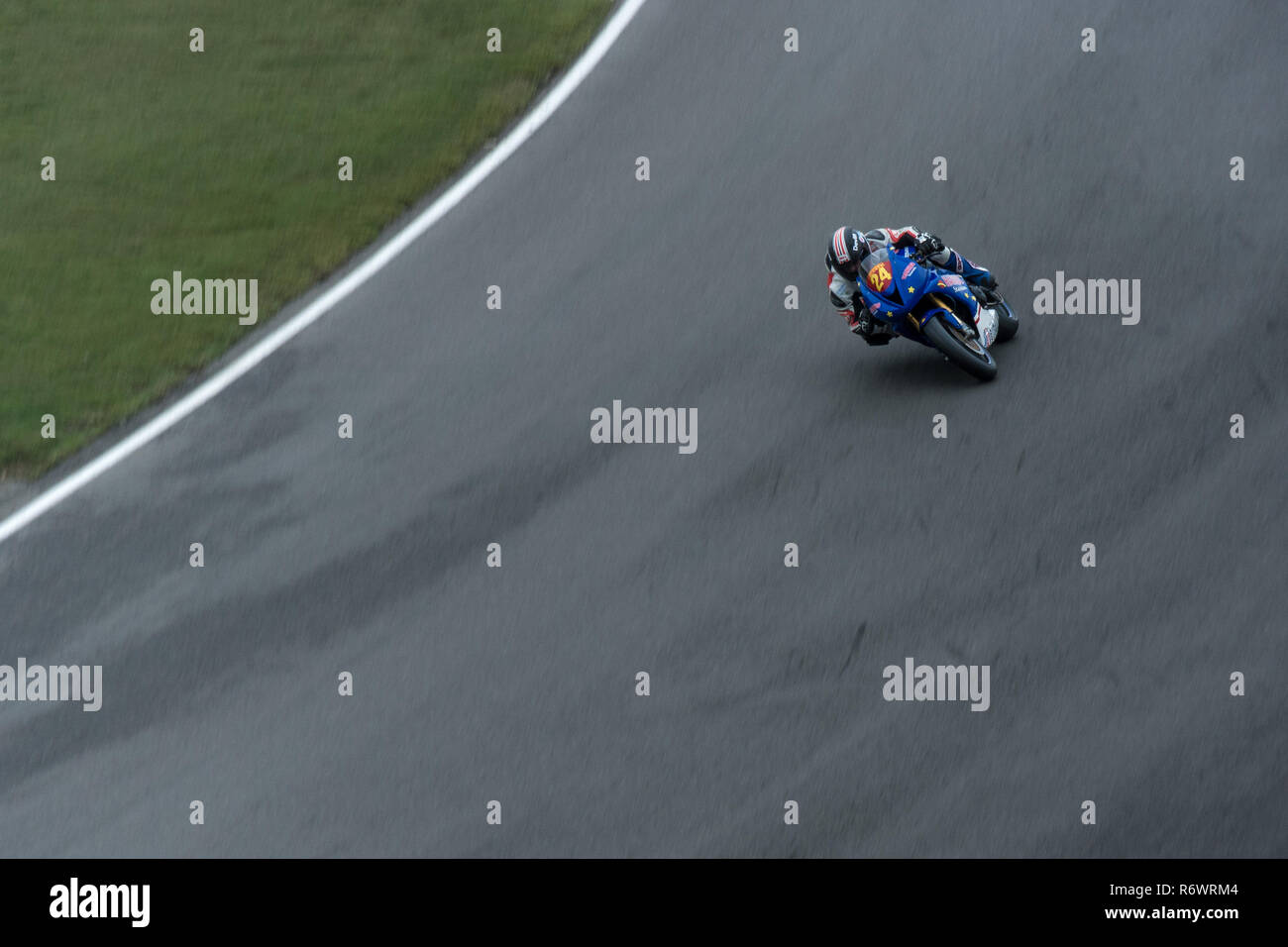 No 24 of the Super Bikes taking a fast downhill bend at Brands Hatch race circuit. - Stock Image