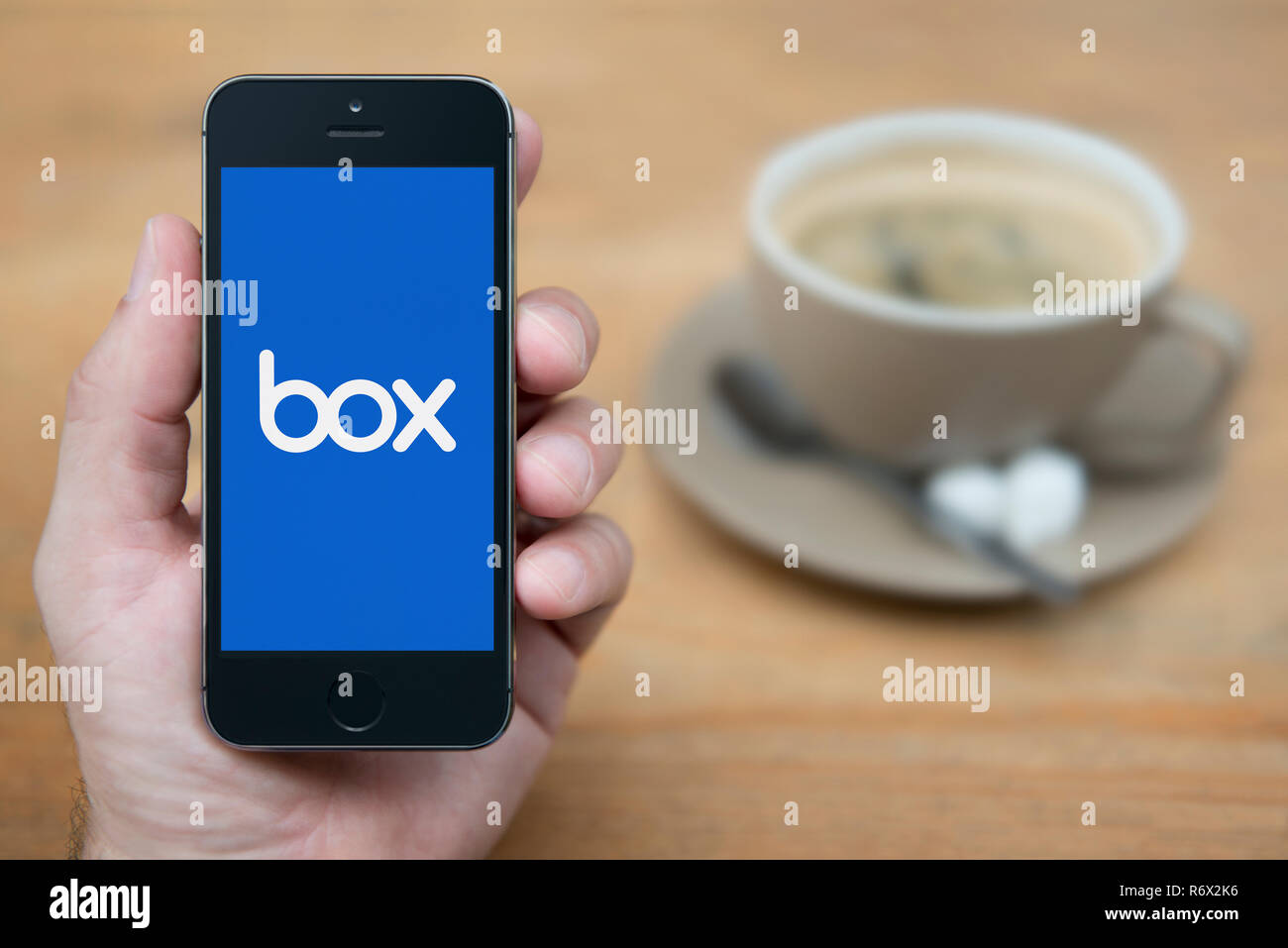 A man looks at his iPhone which displays the Box logo (Editorial use only). - Stock Image