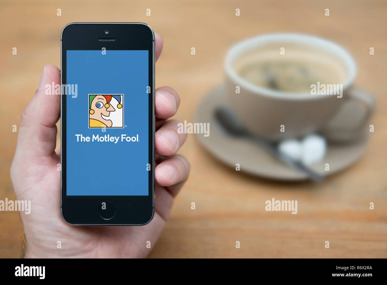 A man looks at his iPhone which displays the Motley Fool logo (Editorial use only). - Stock Image