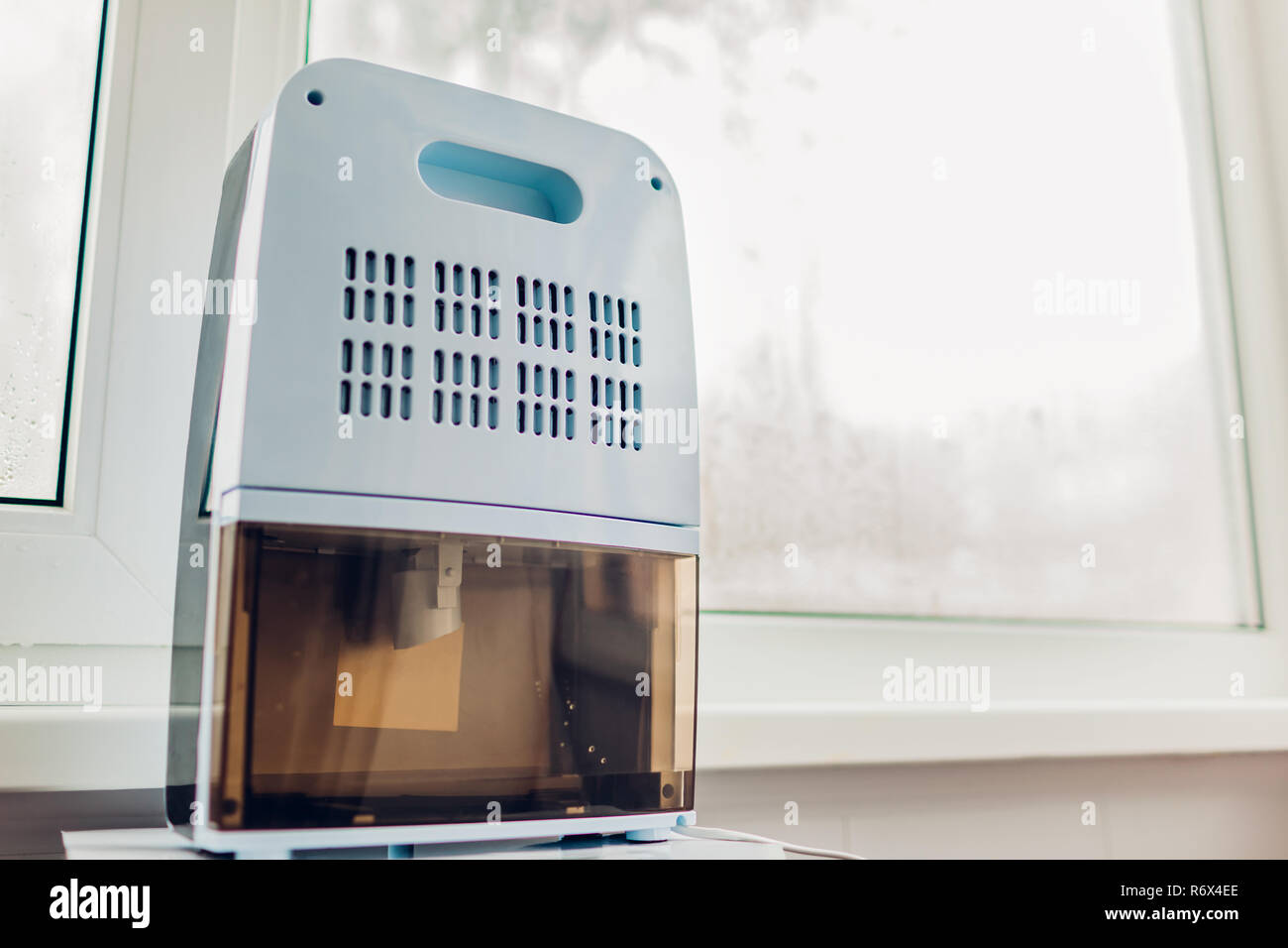 Dehumidifier with touch panel, humidity indicator, uv lamp, air ionizer, water container works by wet window. - Stock Image