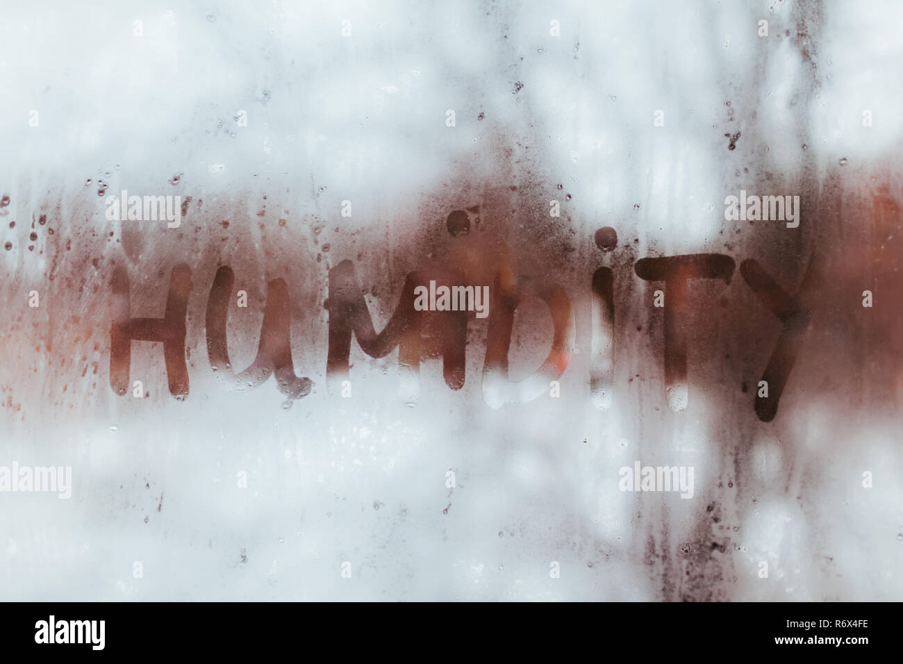 Humidity word written on wet window. High level of dampness in apartment. - Stock Image