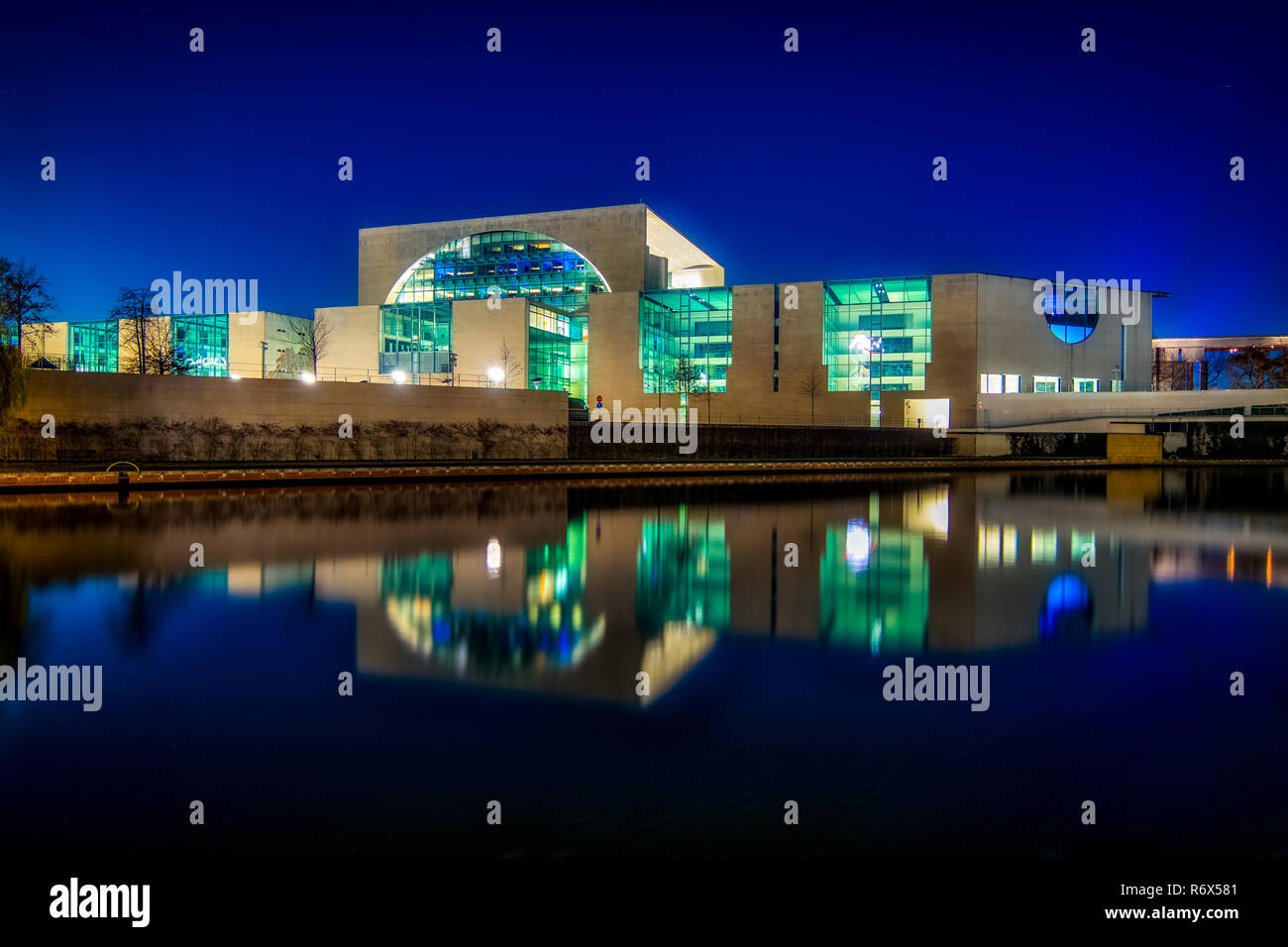 Night shot of the Bundeskanzler amt (chancellor office) seen from the river Spree with reflections in water - Stock Image
