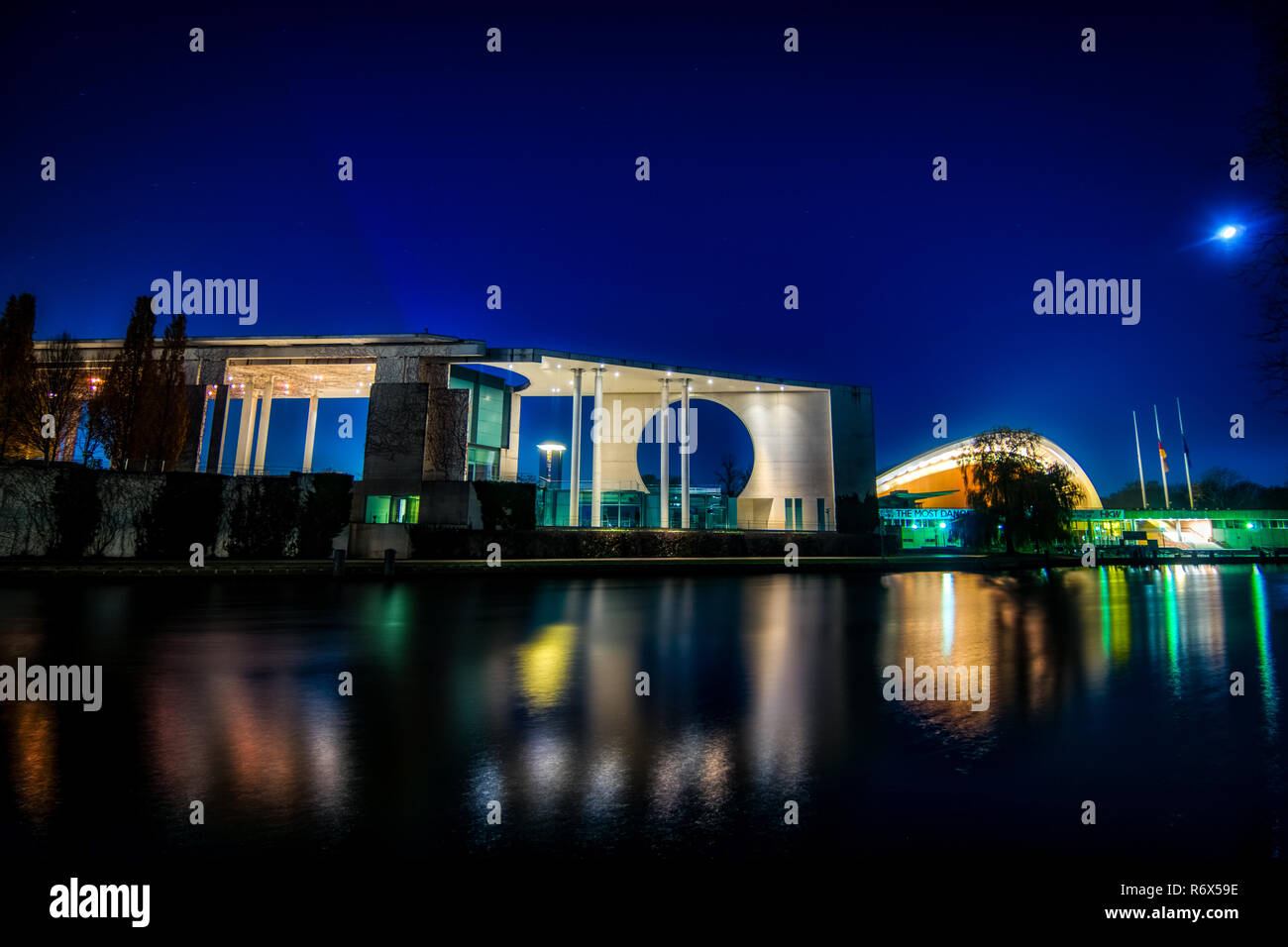 Night shot of the Bundeskanzler amt (chancellor office) and the house of cultures seen from the river Spree with reflections on the water - Stock Image