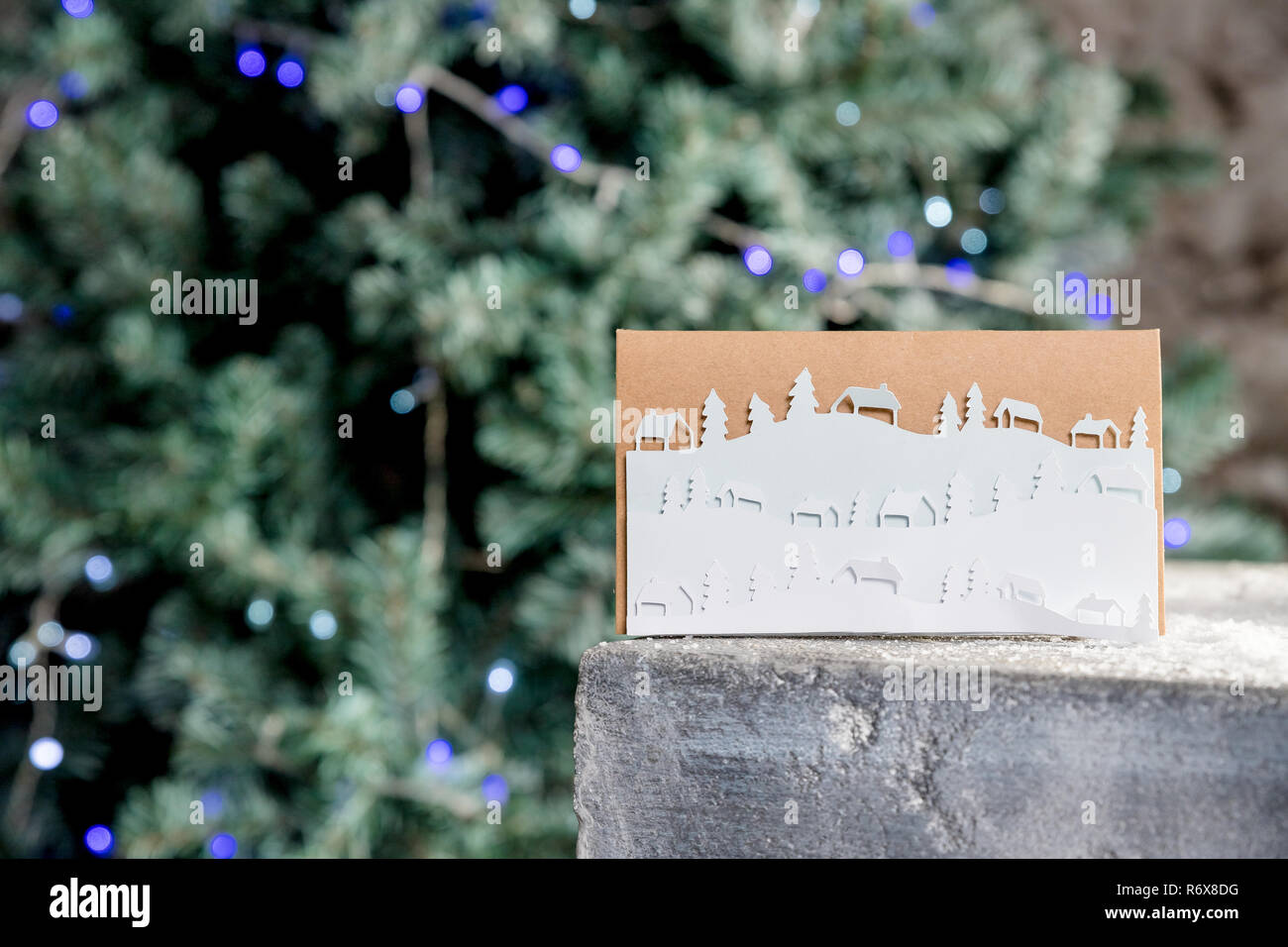 Christmas card with winter landscape.snowflakes,Christmas and Happy new year decoration. DIY concept. Snowy landscape, winter coming. Minimal paper art style.Christmas tree with blue garland lights. - Stock Image