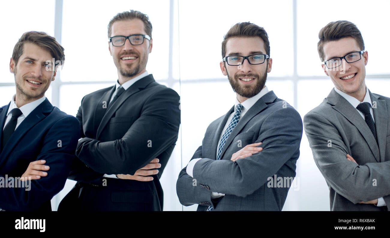 smiling business people standing near the glass wall - Stock Image