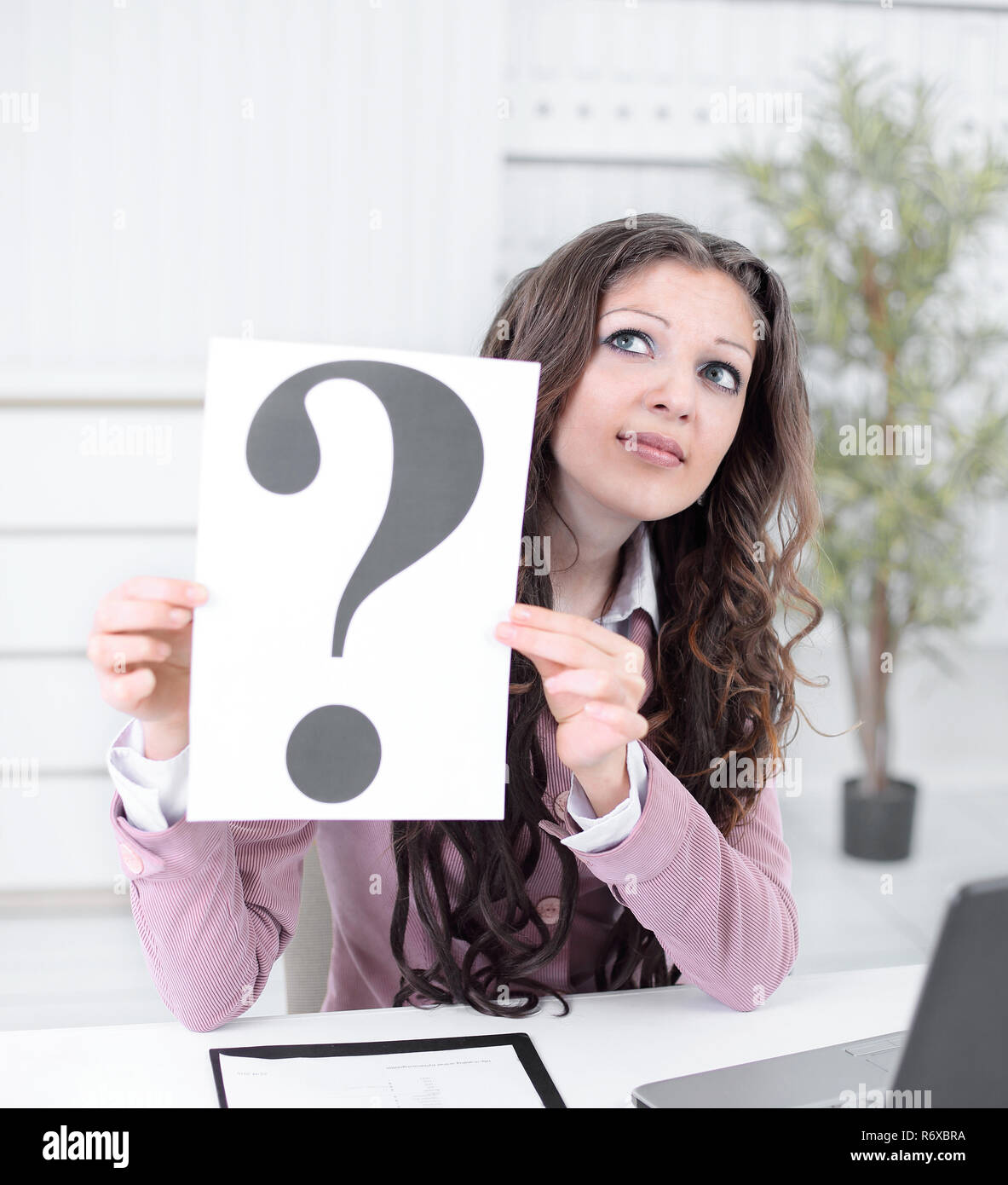 thoughtful business woman showing a question mark - Stock Image