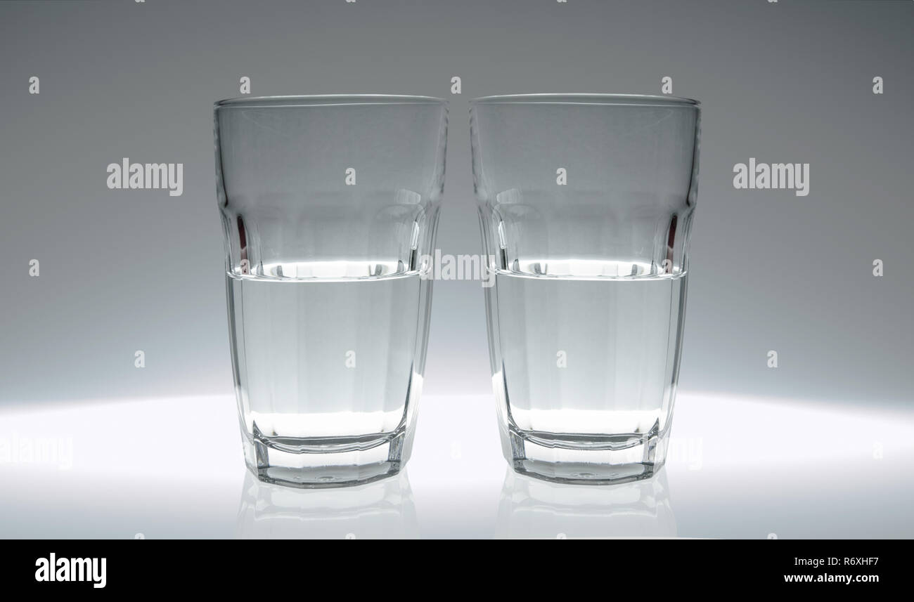 Two glasses of water: one half full, the other half empty. - Stock Image