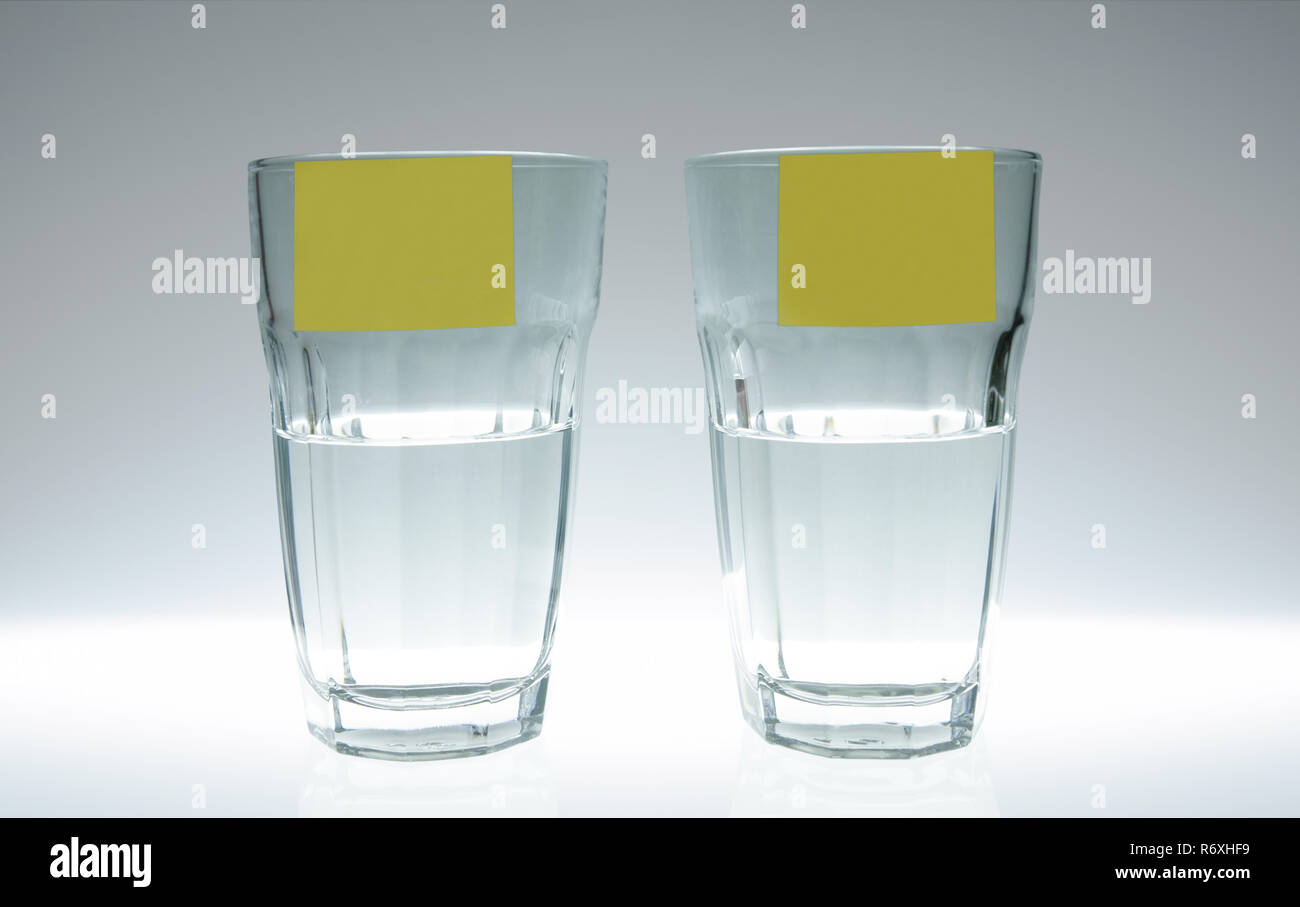Two glasses of water: one half full, the other half empty. On each glass there is a post-it. - Stock Image
