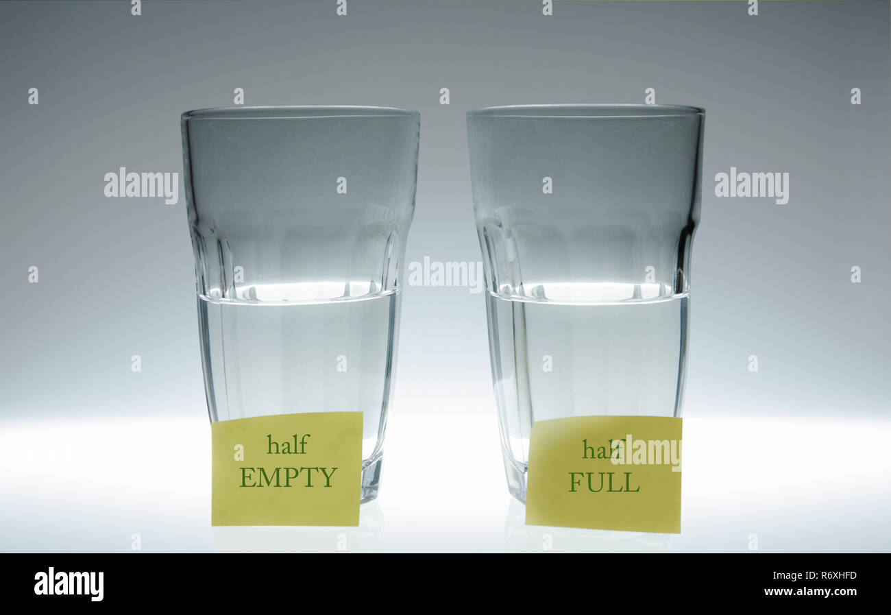 Two glasses of water: one half full, the other half empty. In front of each glass there is a post-it. - Stock Image