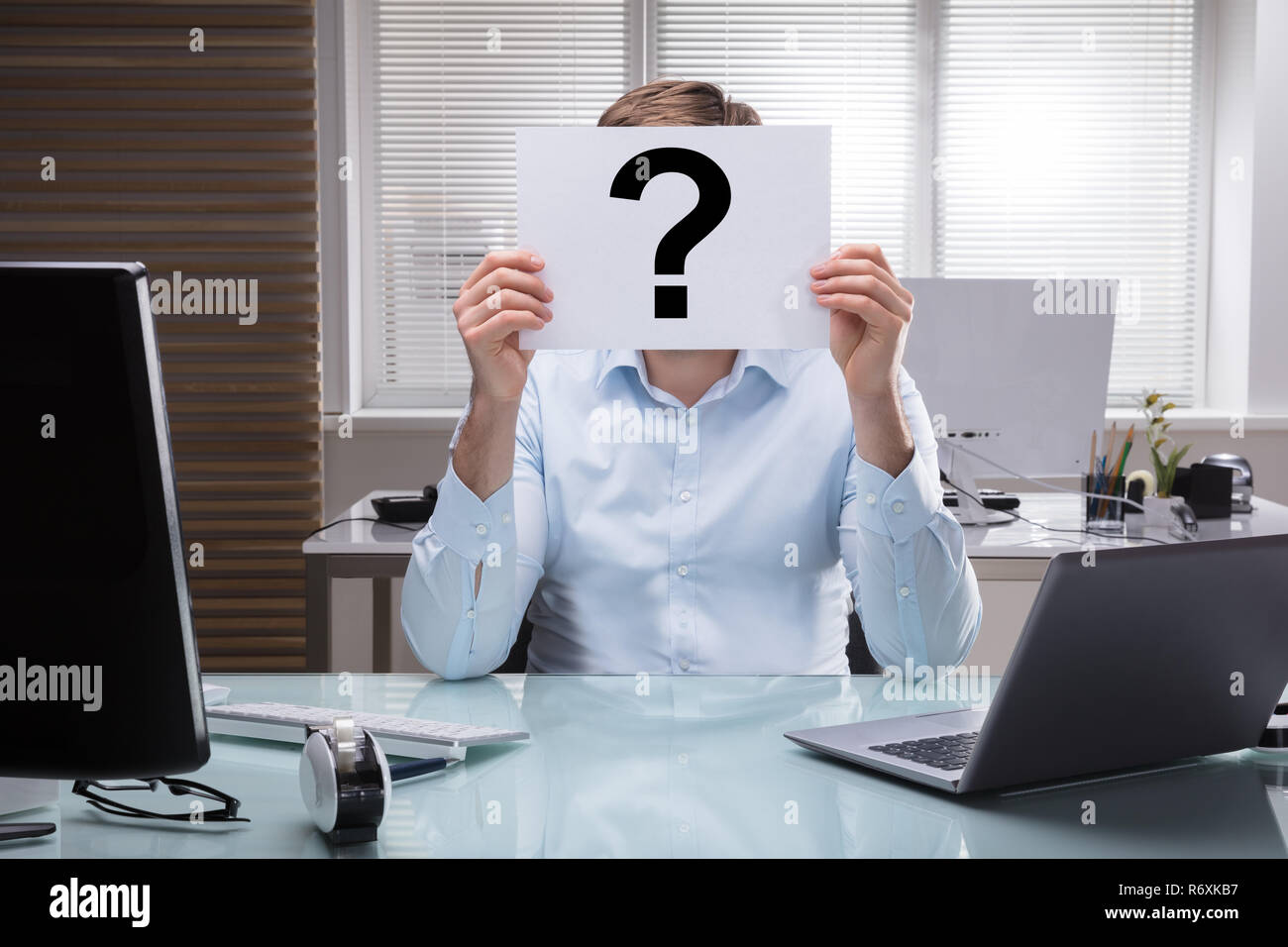 Businessperson Holding Placard With Question Mark Sign - Stock Image