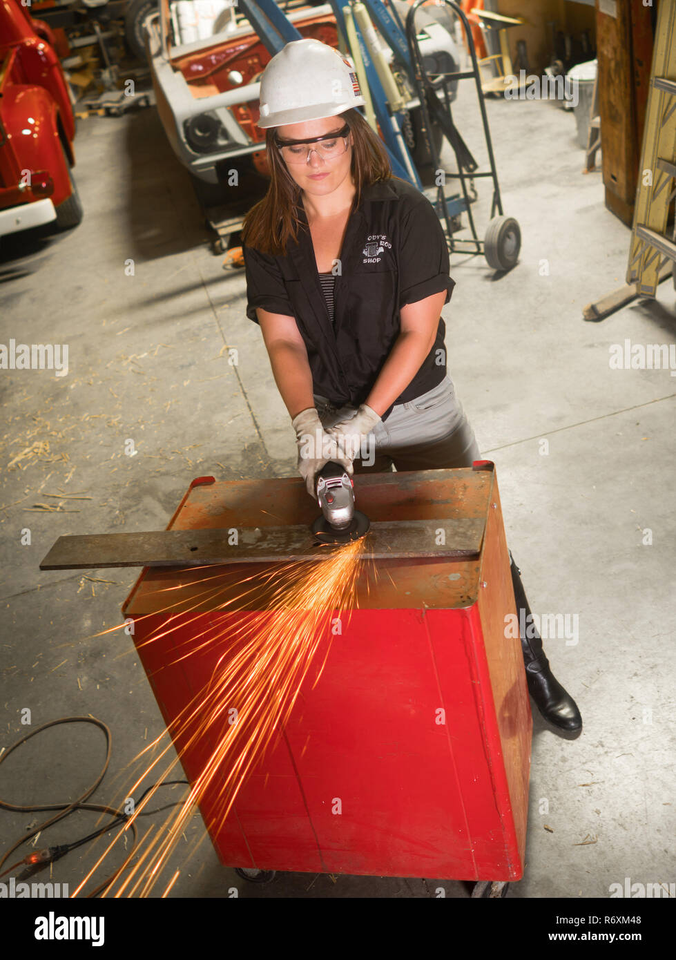 Sparks fly as this young woman grinds a piece of metal in the hot rod shop Stock Photo