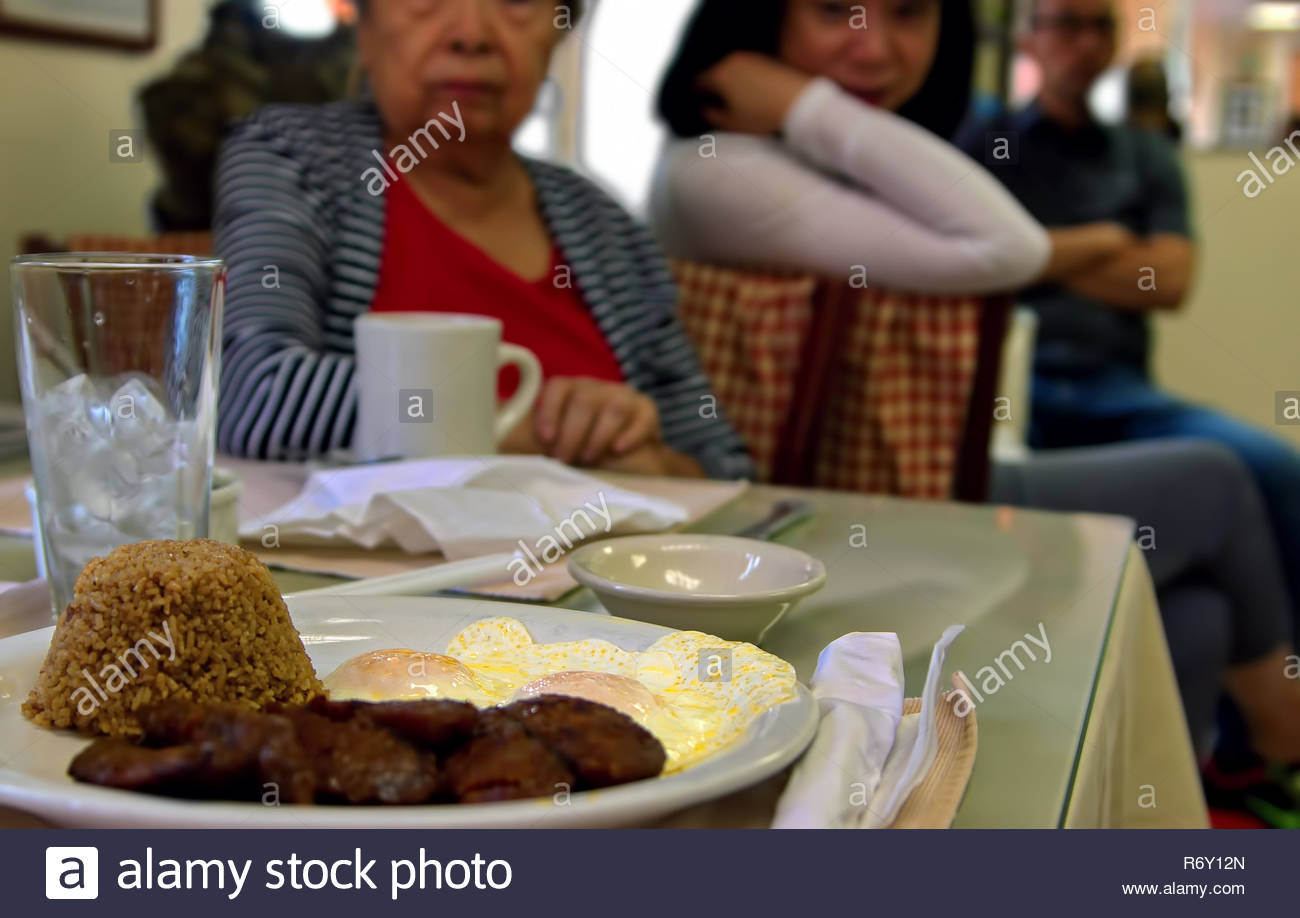 Fairfax, VA USA. Aug 2014. Asian American family eagerly waiting to dig in to a typical Filipino breakfast of sausage, eggs, and fried rice. - Stock Image