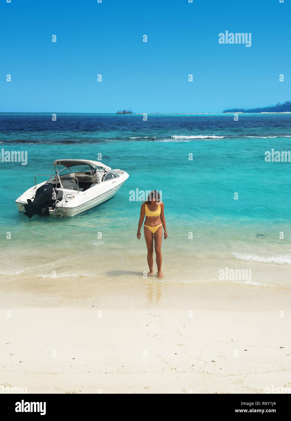 female on the beach and speedboat, luxury resort Maldives - Stock Image