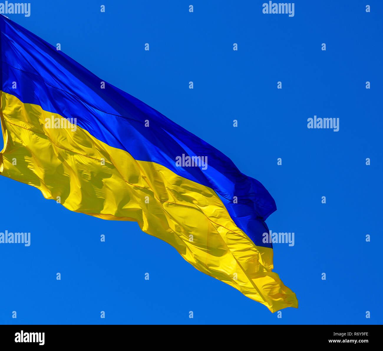 textile flag of Ukraine develops against a clear blue sky Stock Photo