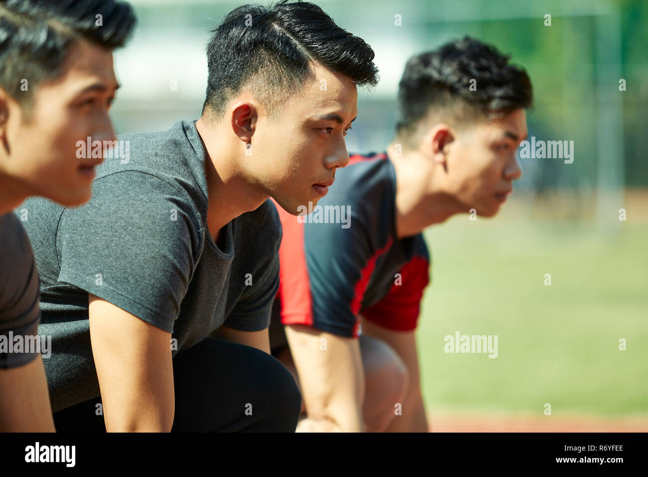 young asian track and field athletes sprinters setting on starting line. - Stock Image