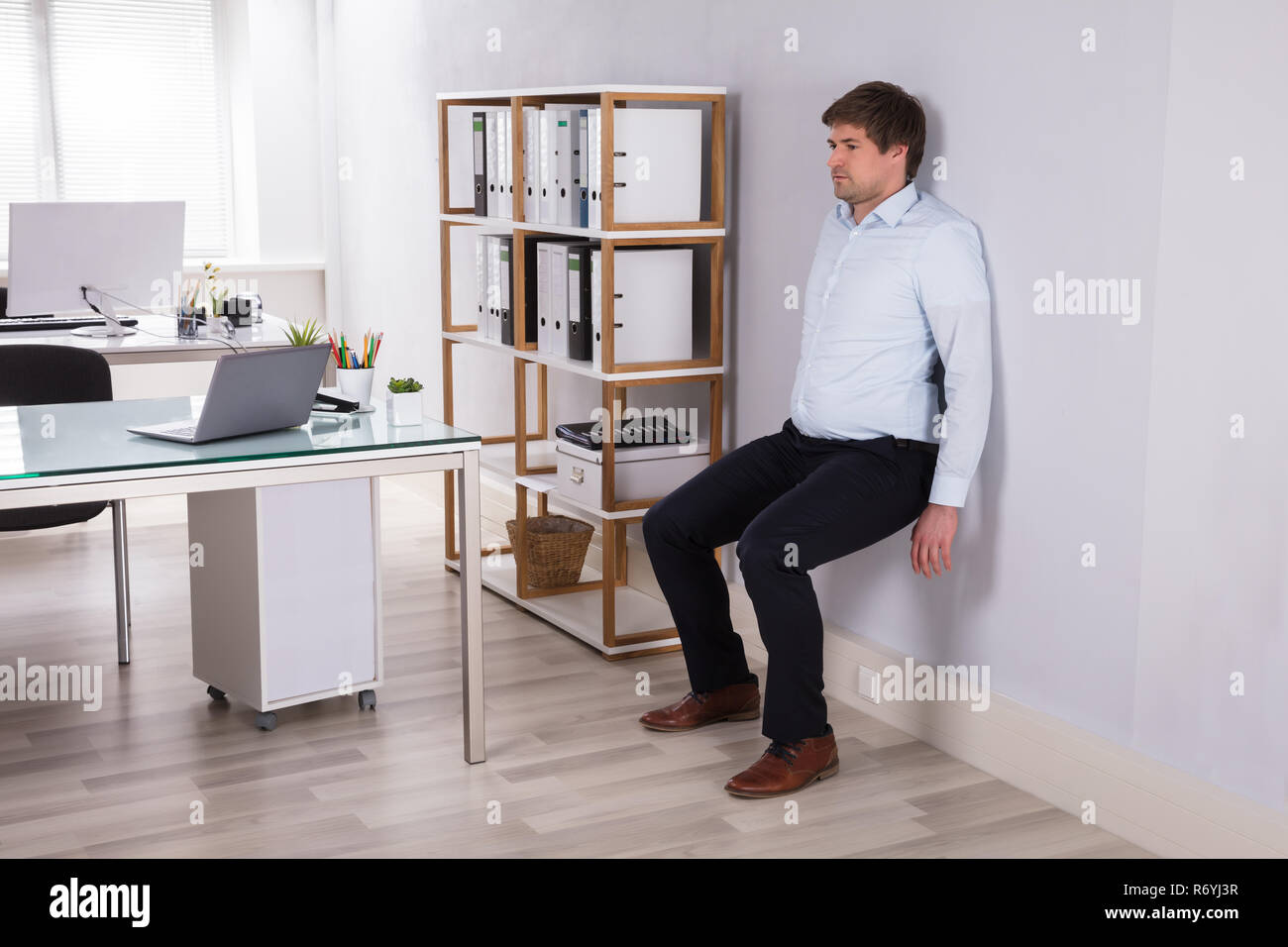 Businessman Leaning On Wall Doing Workout - Stock Image