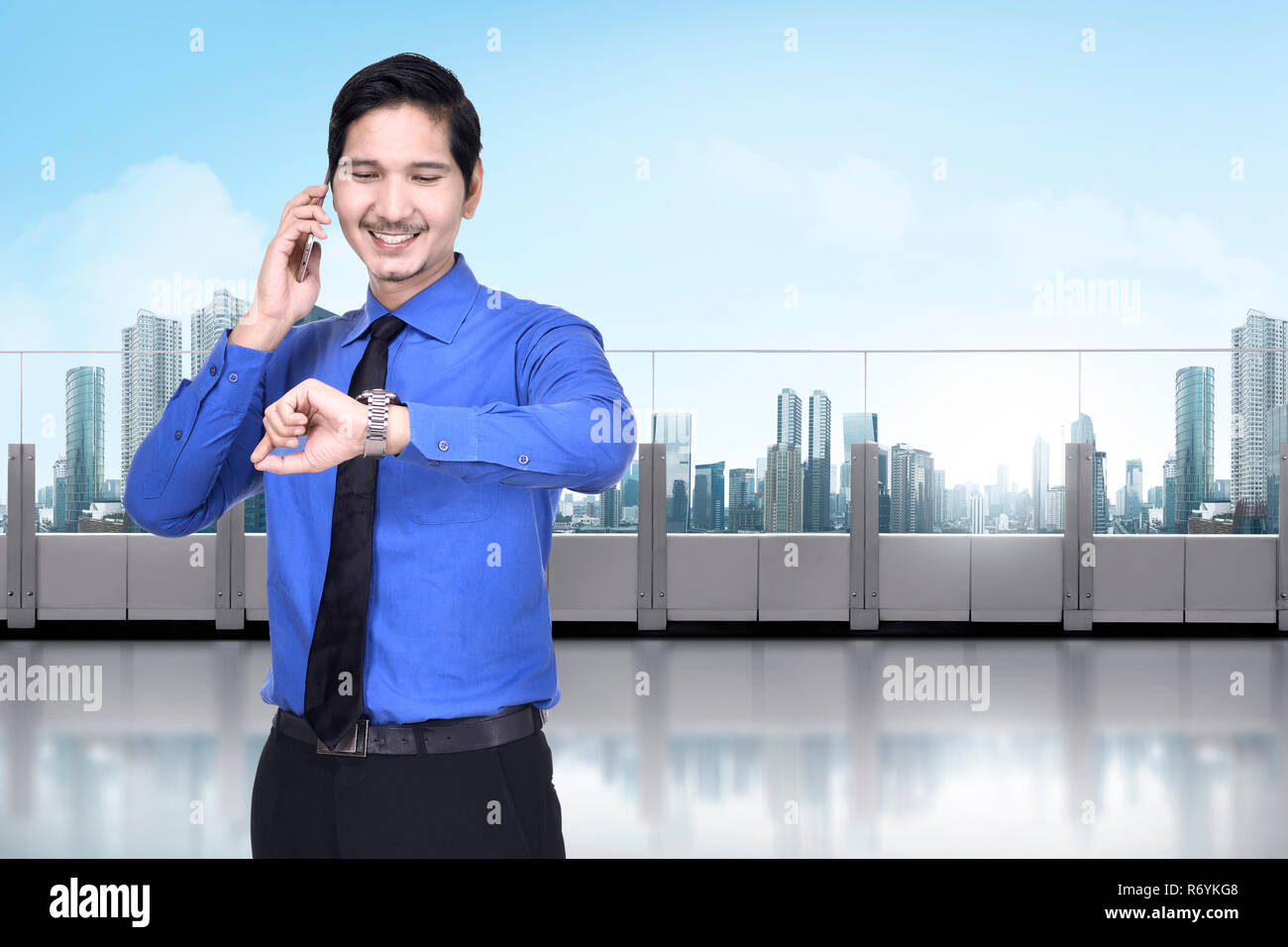 Happy asian businessman with phone checking the watch Stock Photo