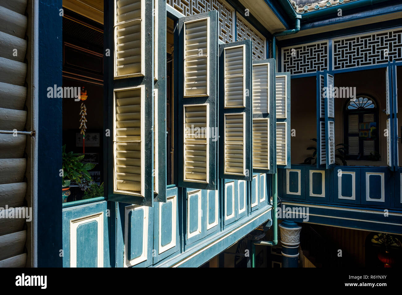 Tourquoise and yellow wooden shutters on upper (first) floor, Tjong A Fie Mansion, Medan, North Sumatra, Sumatra, Indonesia. - Stock Image