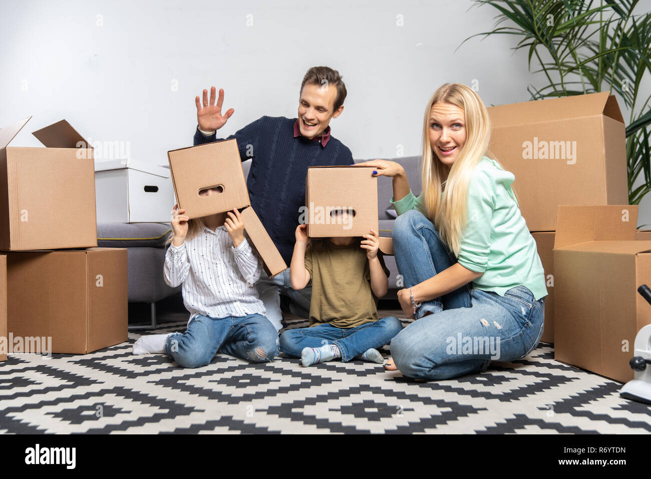 Image of young married couple with indulging children sitting on floor among cardboard boxes in new apartment - Stock Image