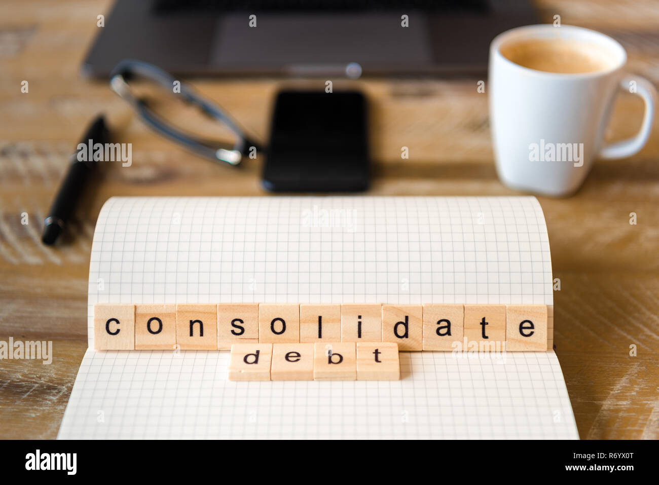 Closeup on notebook over wood table background, focus on wooden blocks with letters making Consolidate Debt words - Stock Image