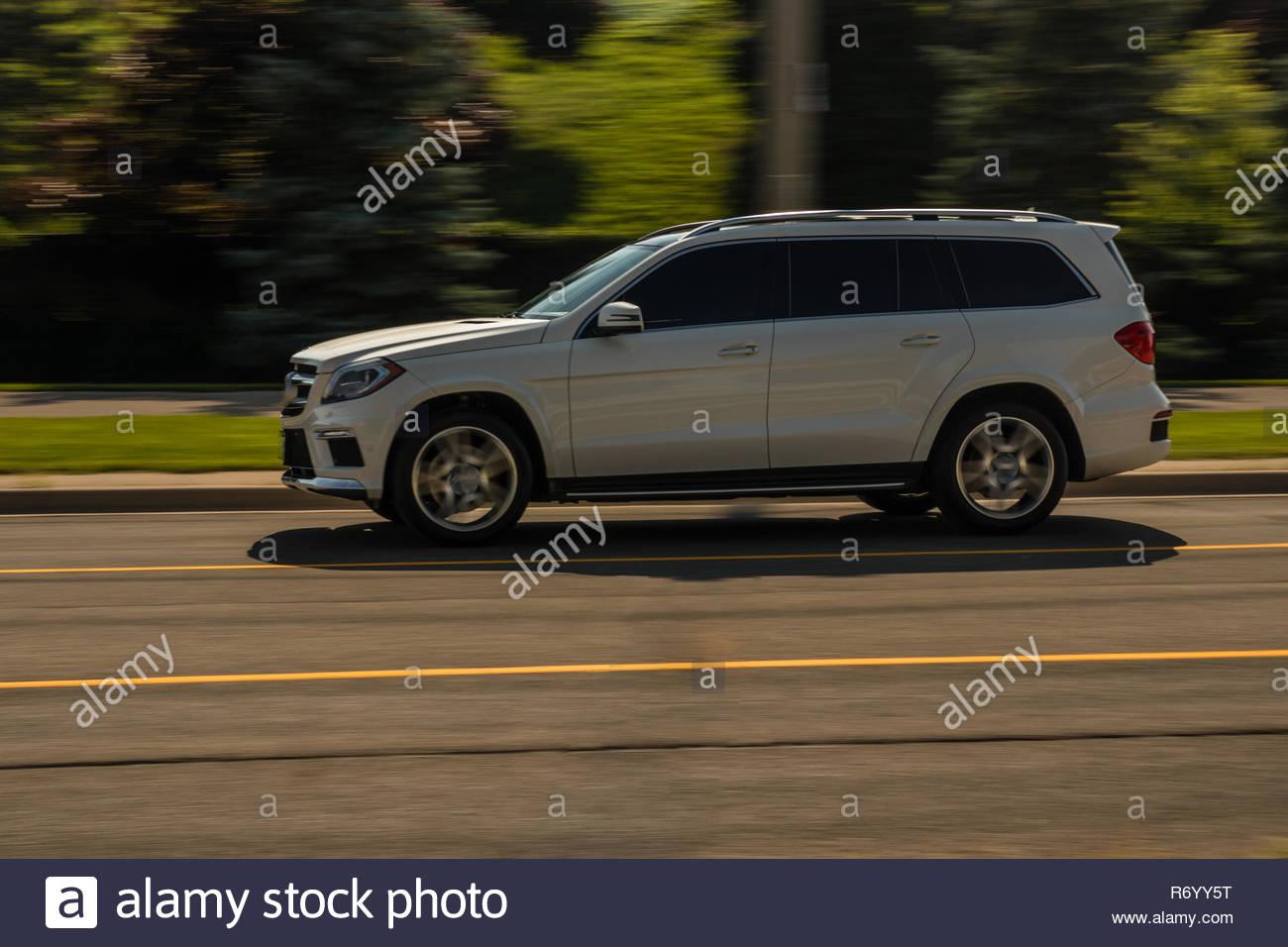 Speeding white SUV zipping near the Golf course - Stock Image