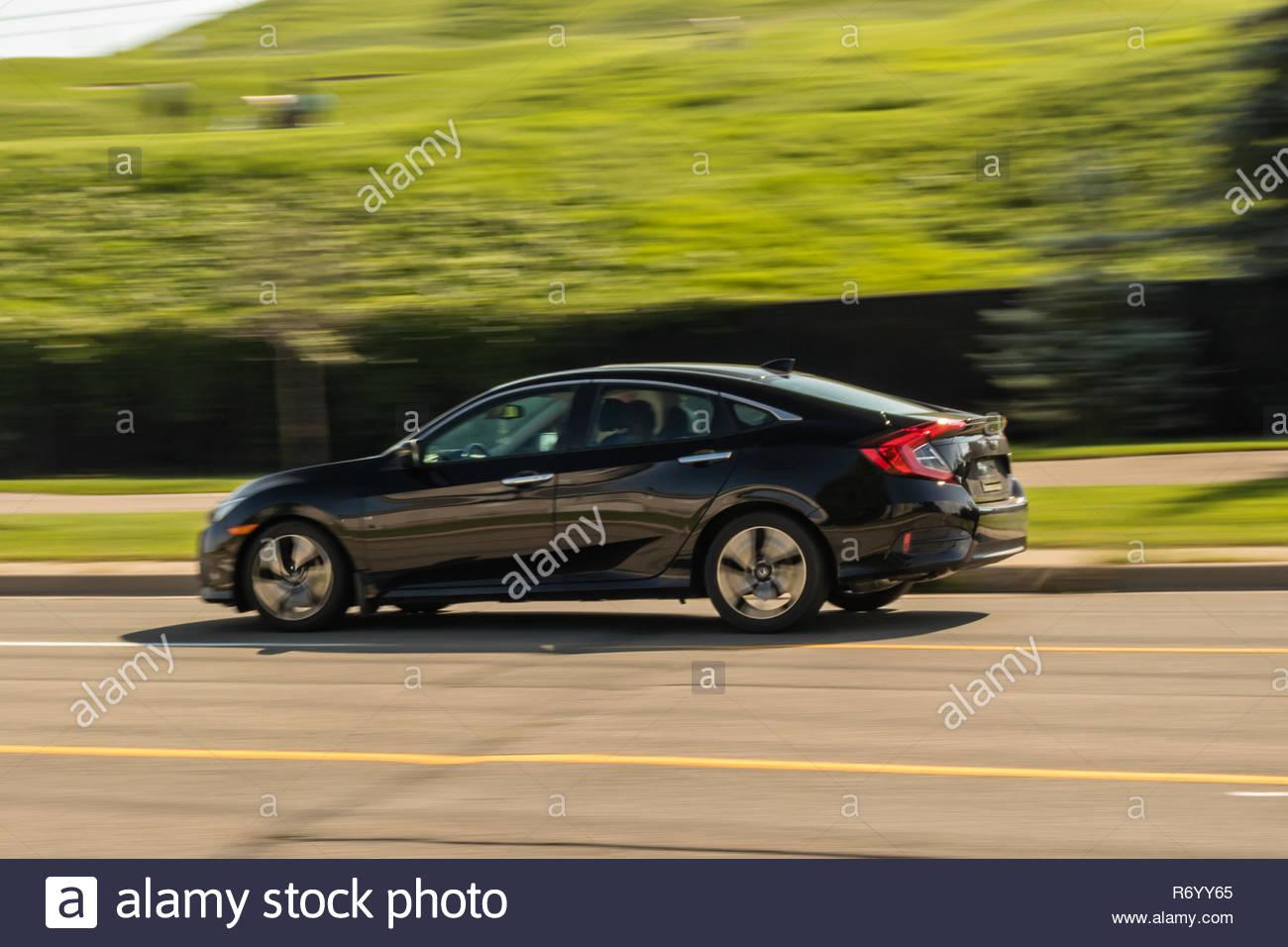 Speeding black full size car - Stock Image