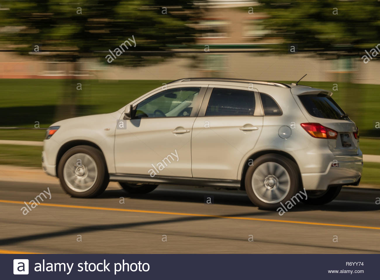 White SUV zipping through the streets - Stock Image