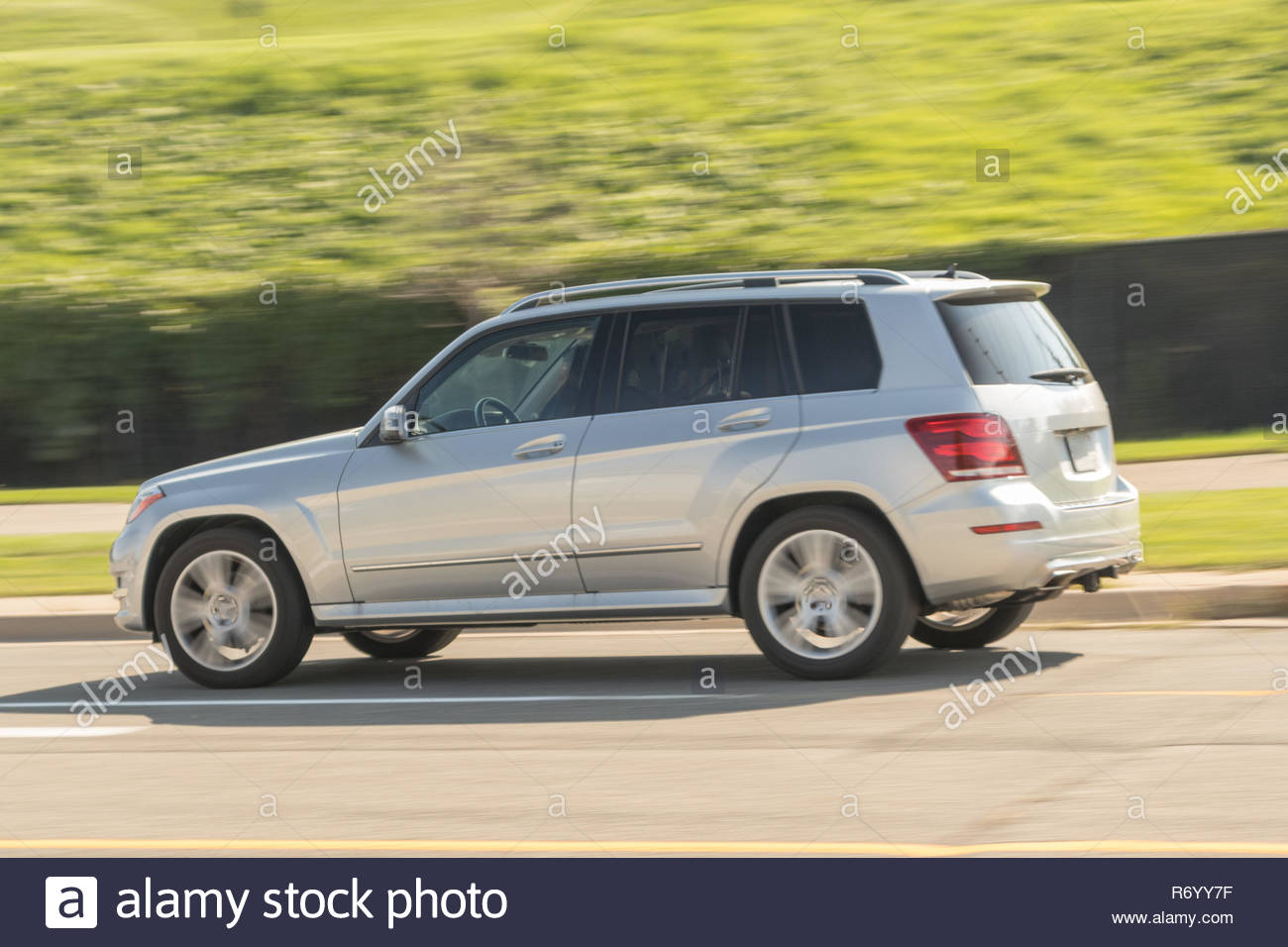 Silver SUV zipping through the streets - Stock Image