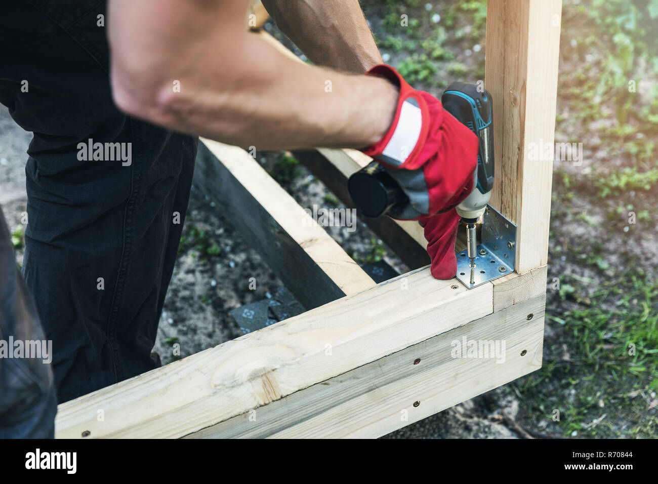 wood shed construction - man screwing corner joint brace - Stock Image