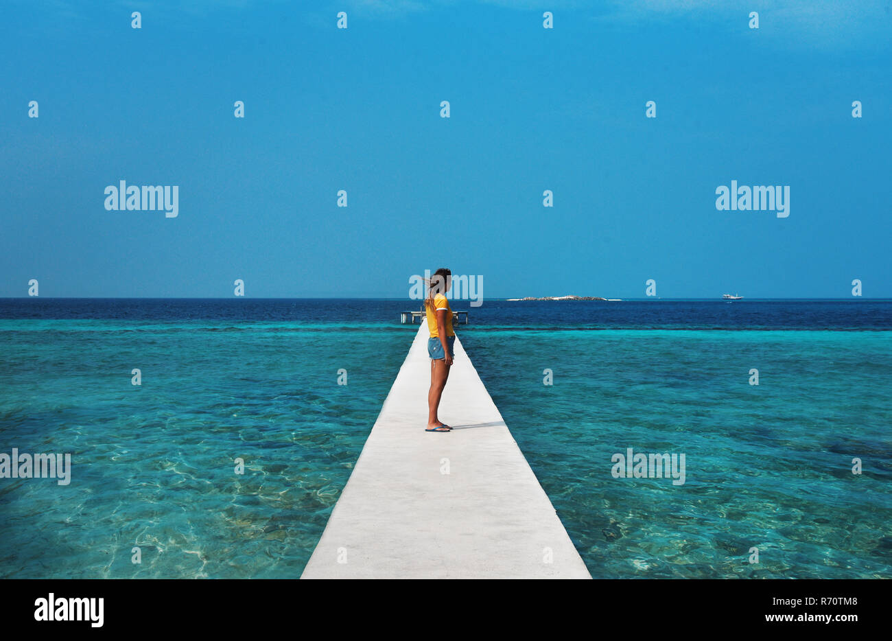 Female looking out to sea surrounded by reef on holiday in Maldives - Stock Image