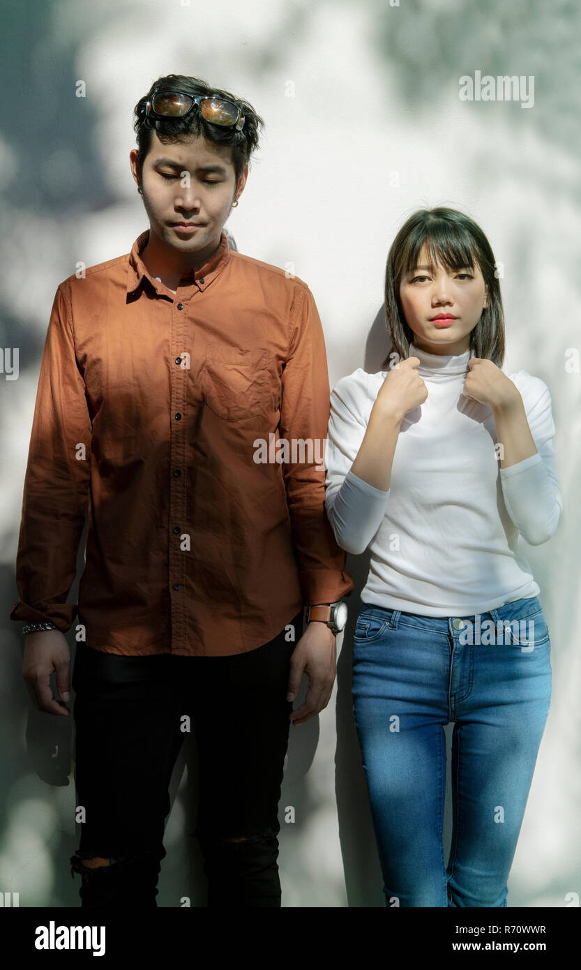 portrait of asian younger man and woman like fashion model standing against beautiful light wall - Stock Image