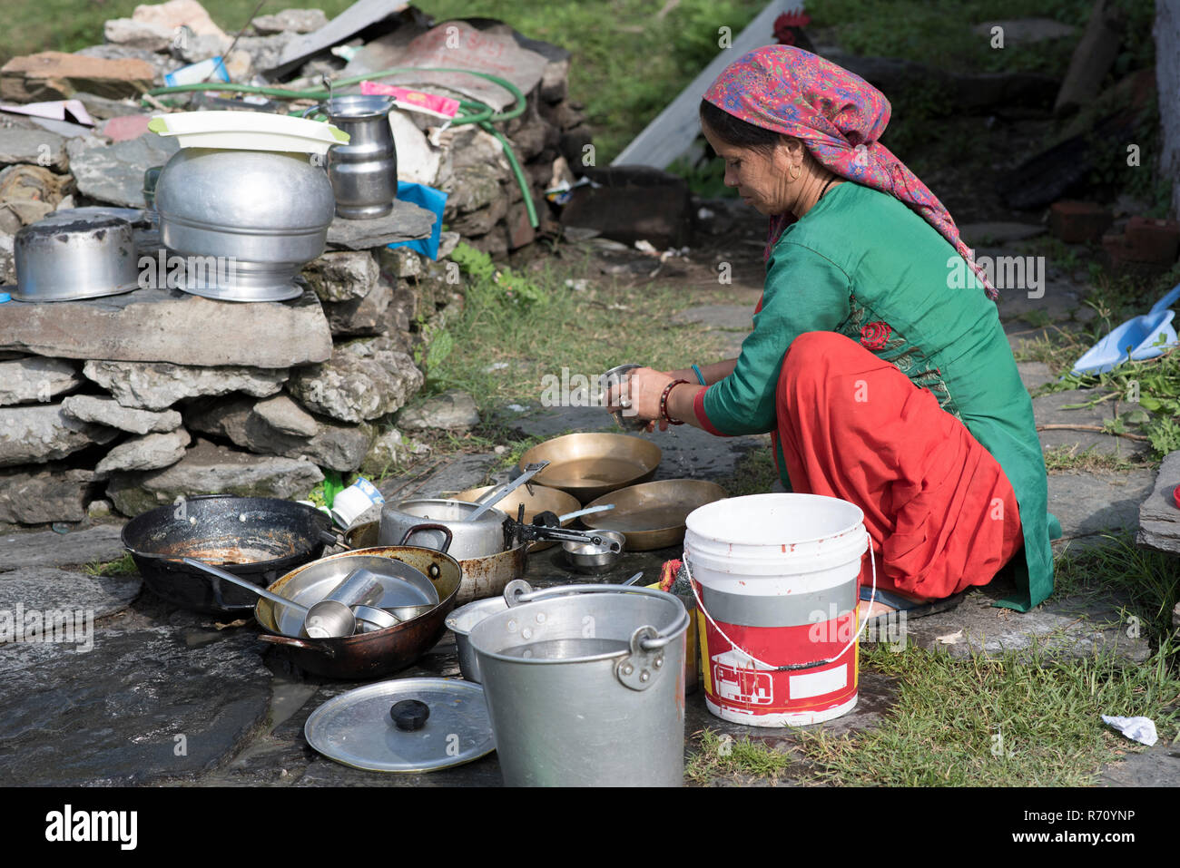Woman cleaning utensils outdoors in Shimla, Himachal Pradesh, India. - Stock Image