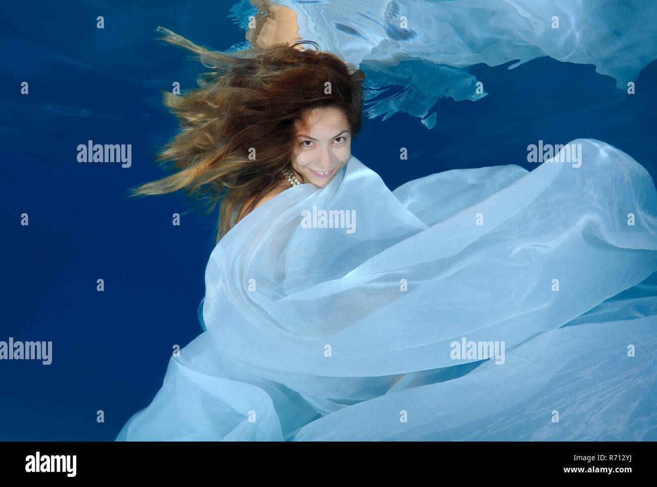 Woman in a long white dress under water, underwater fashion