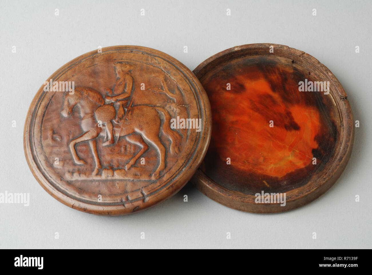Wooden snuff box with rider embossed on the lid, snuffbox holder walnut wood turtle, Round. Wood on the outside; turtle inside. On the cover of man on horseback Frederick the Great King of Prussia. Snuff box personal attribute personal equipment smokehouse tobacco snuff sniffing keep tobacco box animal material keratin - Stock Image