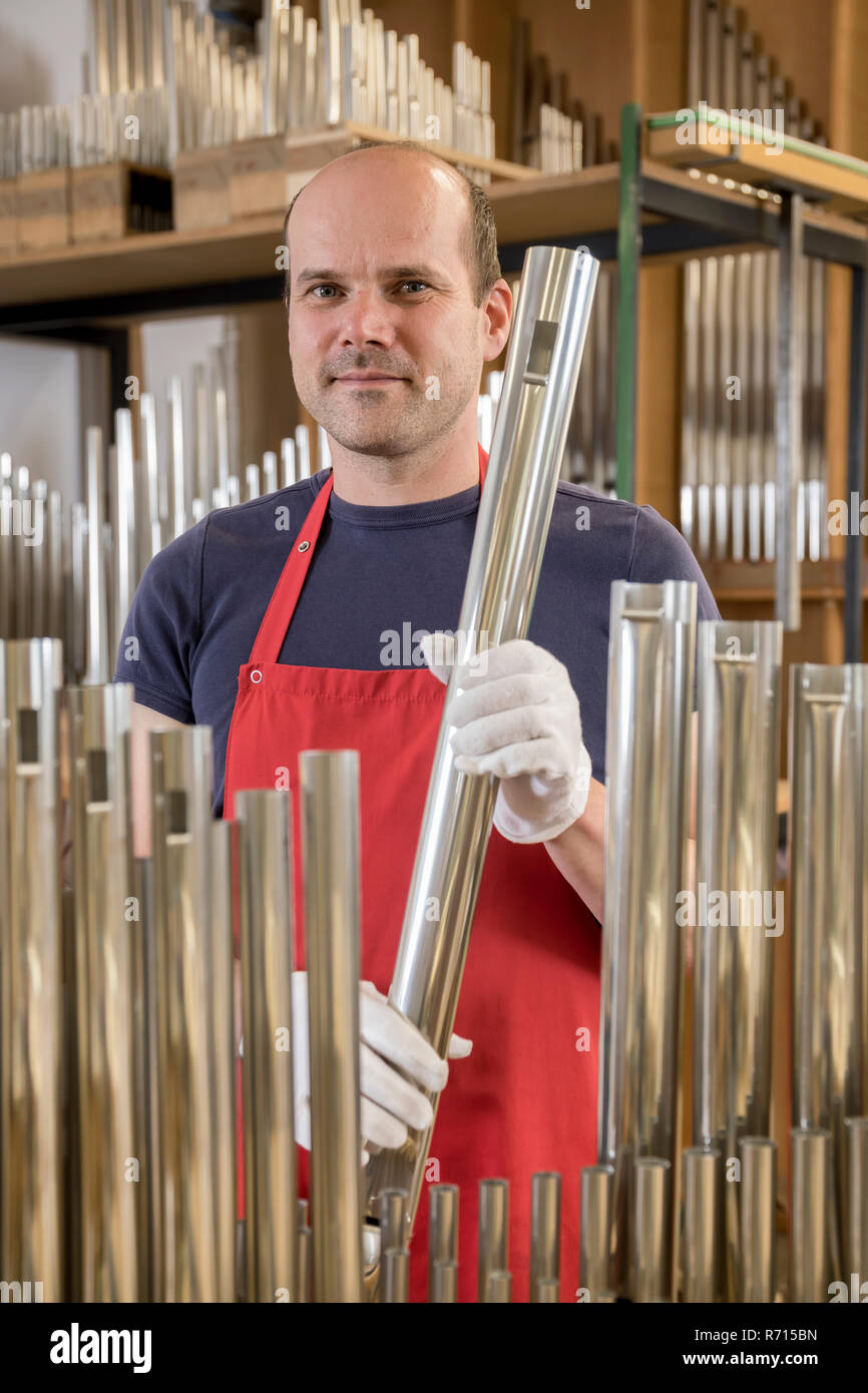 Organ builder, holds an organ pipe of an organ, Laberweinting, Bavaria, Germany - Stock Image