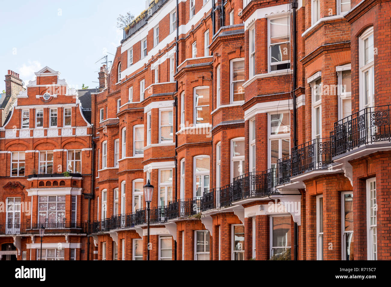 Row of houses with red brick building in Victorian style, district Kensington, London, United Kingdom - Stock Image