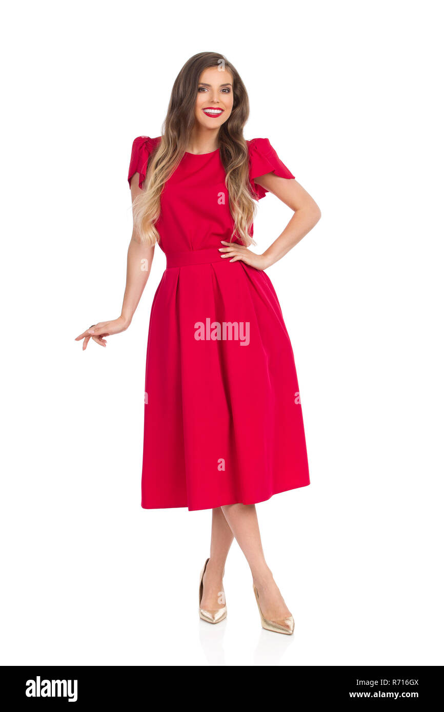 Beautiful young woman in red dress and gold high heels is standing with legs crossed, looking at camera and smiling. Full length studio shot isolated  - Stock Image