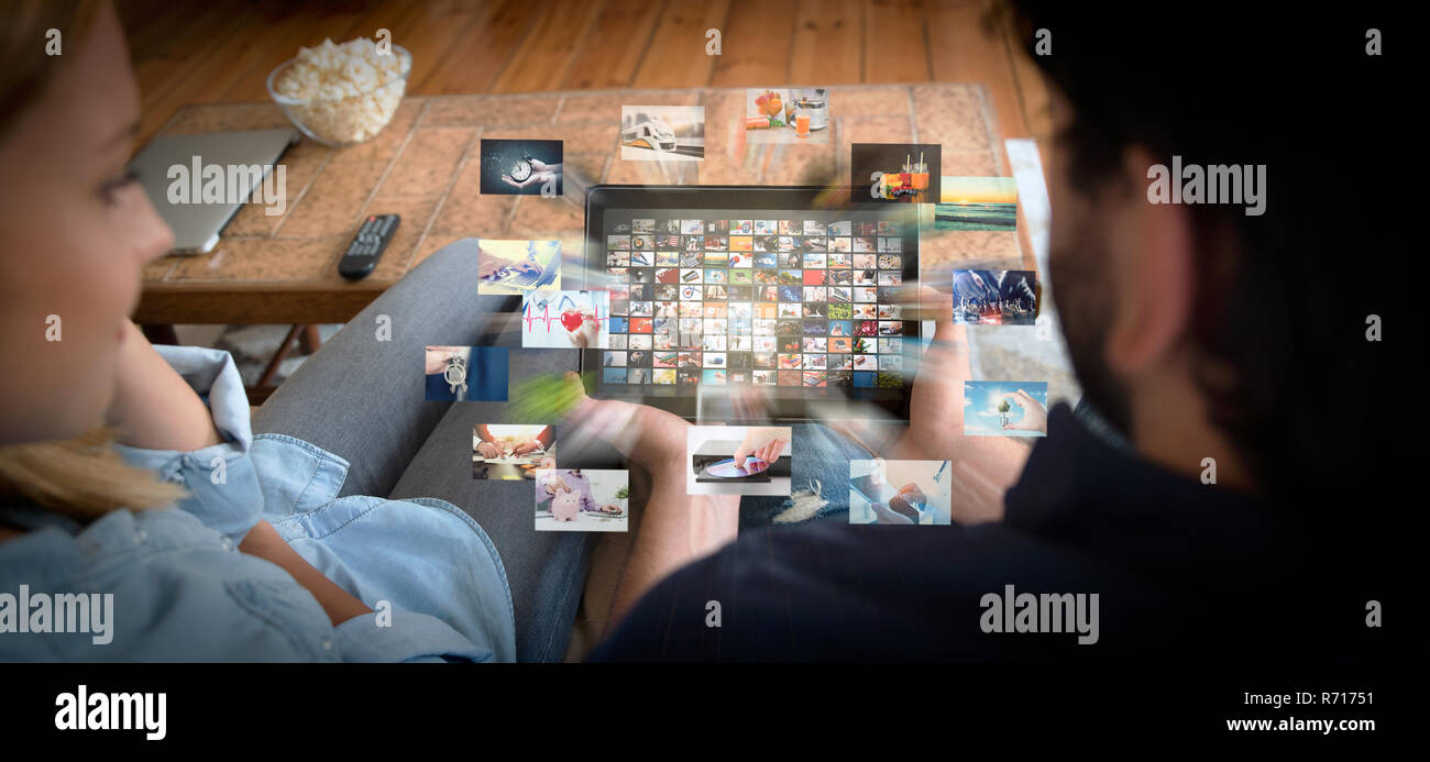 Couple using tablet for watching VOD service. Video On Demand television with abstract flying images - Stock Image