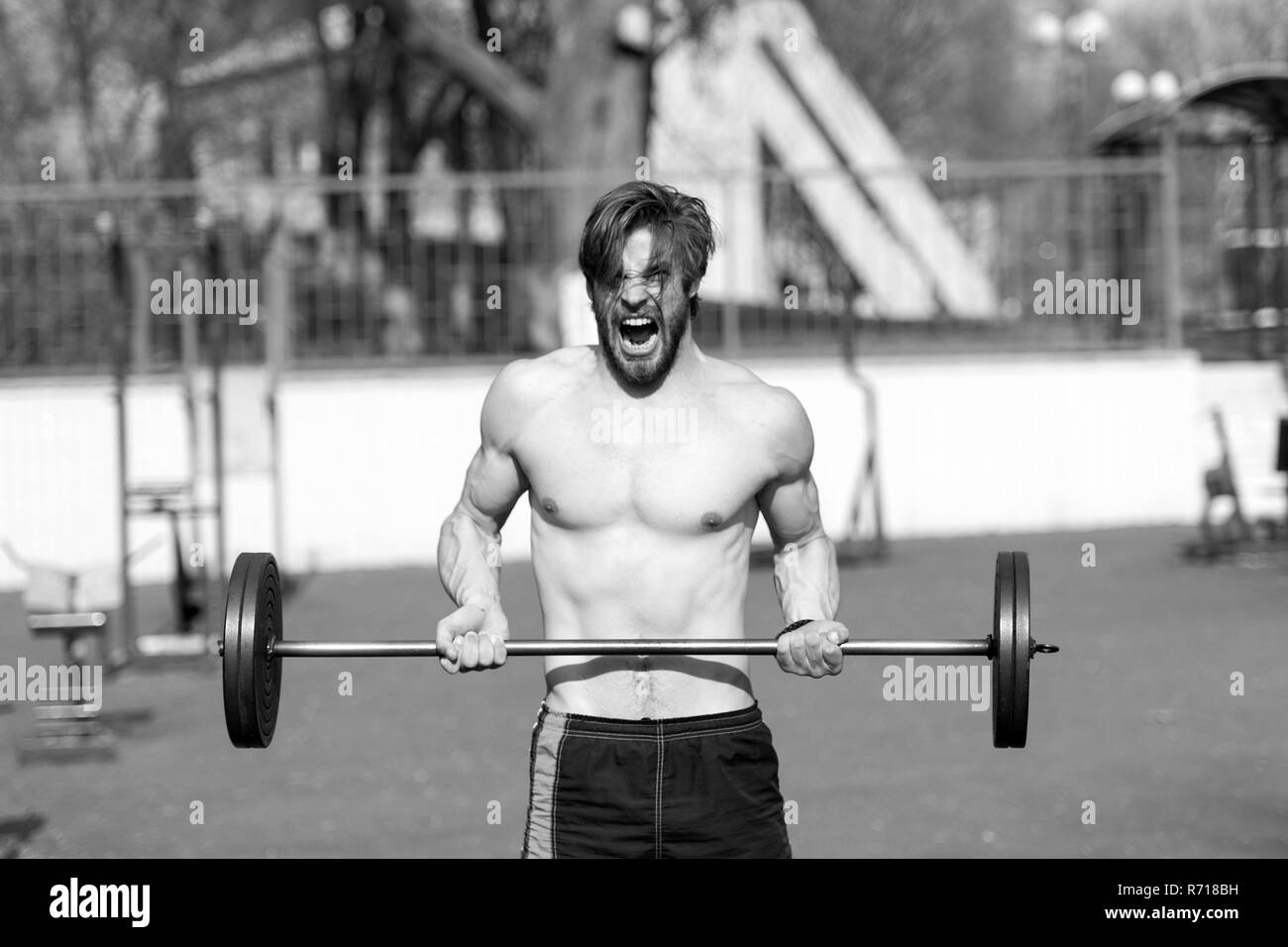 Sportsman lift barbell on stadium. Man with athletic torso, strong arms. Athlete shout training with weight. Weightlifting, bodybuilding, fitness, sport. Power, energy, strength concept - Stock Image