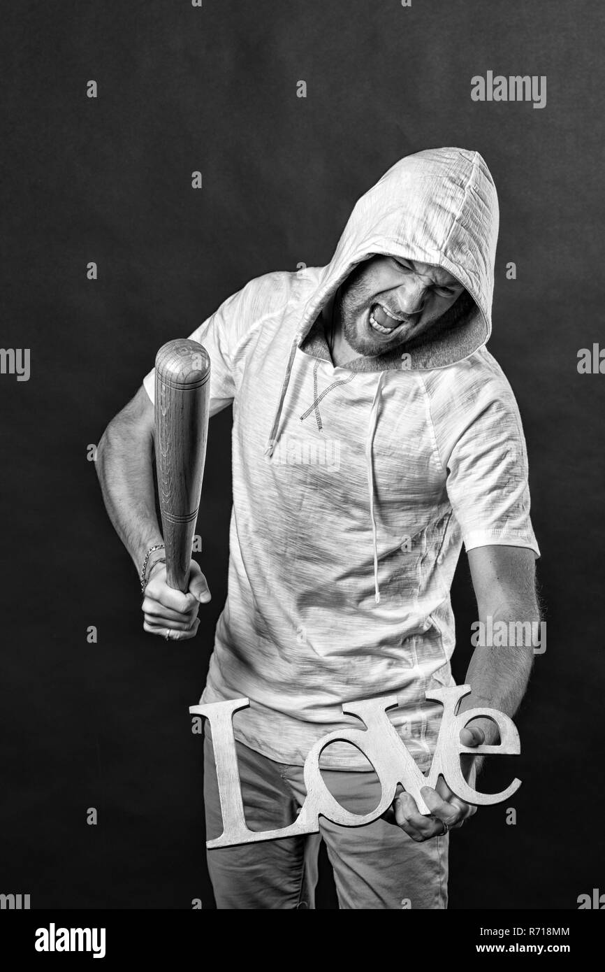 No love and hate concept. Man in hood bat love word. Angry hooligan with baseball bat. Divorce and break up. Anti valentines day, black and white. - Stock Image