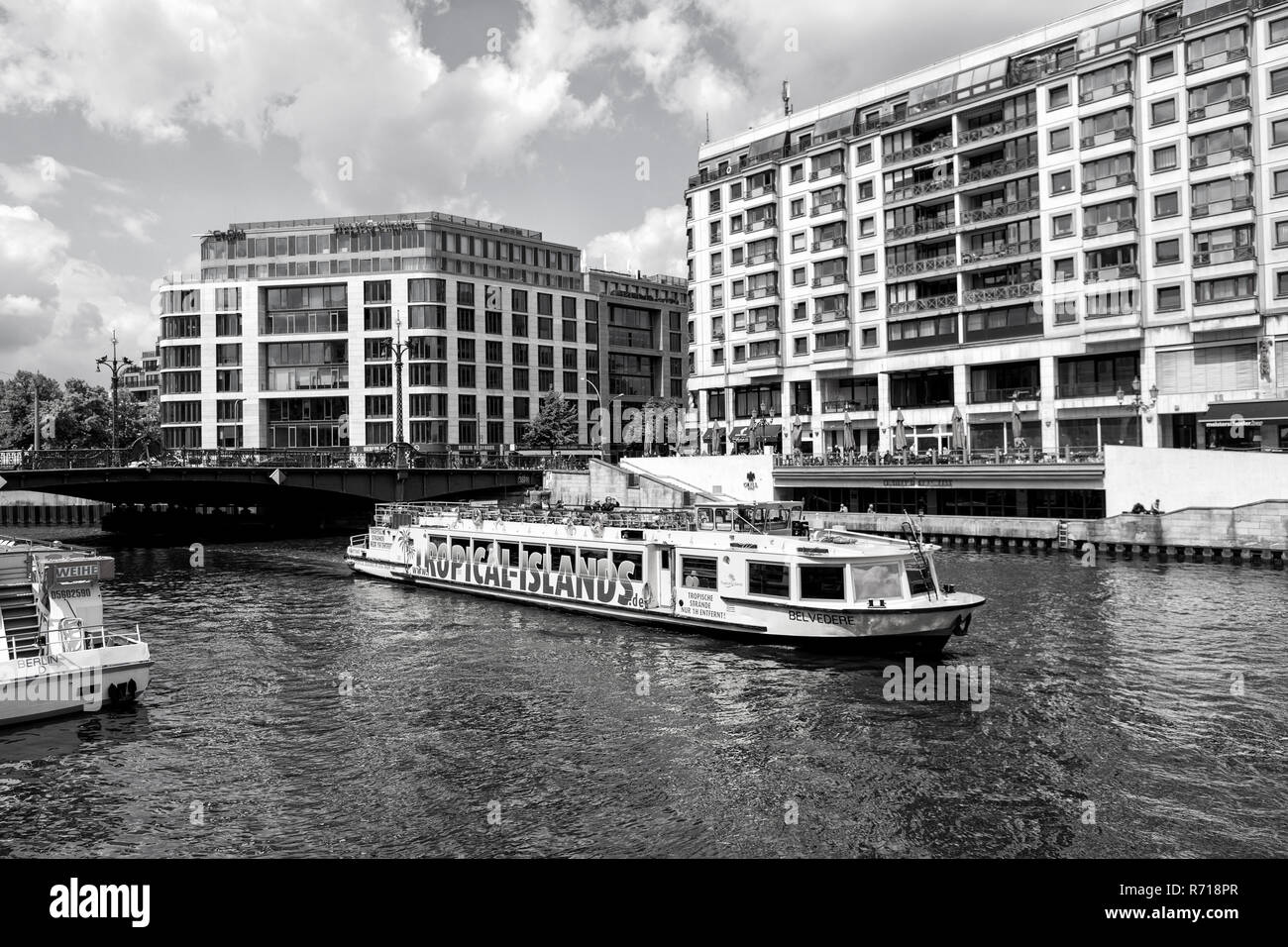 Berlin, Germany - May 31, 2017: tourist ship on river water on cloudy sky on city skyline background. Travelling and boat trip, concept - Stock Image