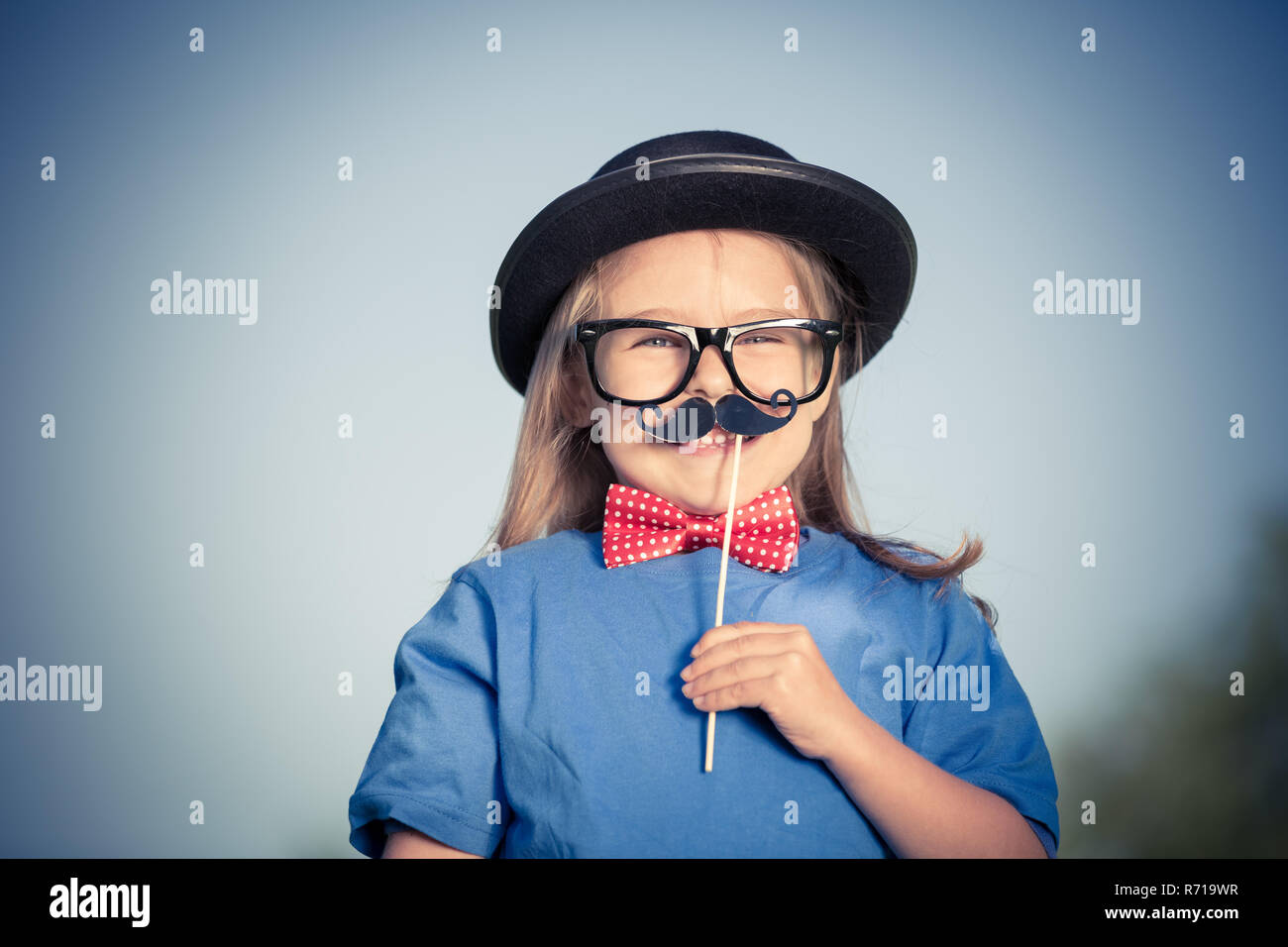 Funny happy little girl in bow tie and bowler hat. - Stock Image