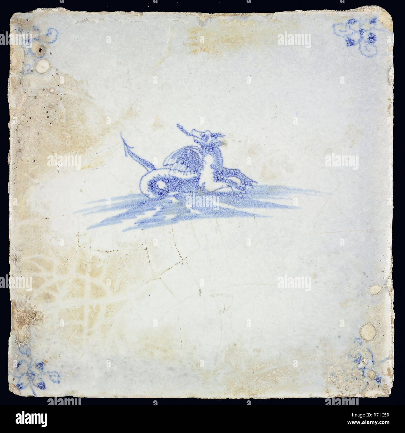 Sea creature tile, in blue on white, dragon-like creature with wings and pintail in water to the right, corner pattern spider, wall tile tile sculpture ceramic earthenware glaze, baked 2x glazed painted mythology - Stock Image